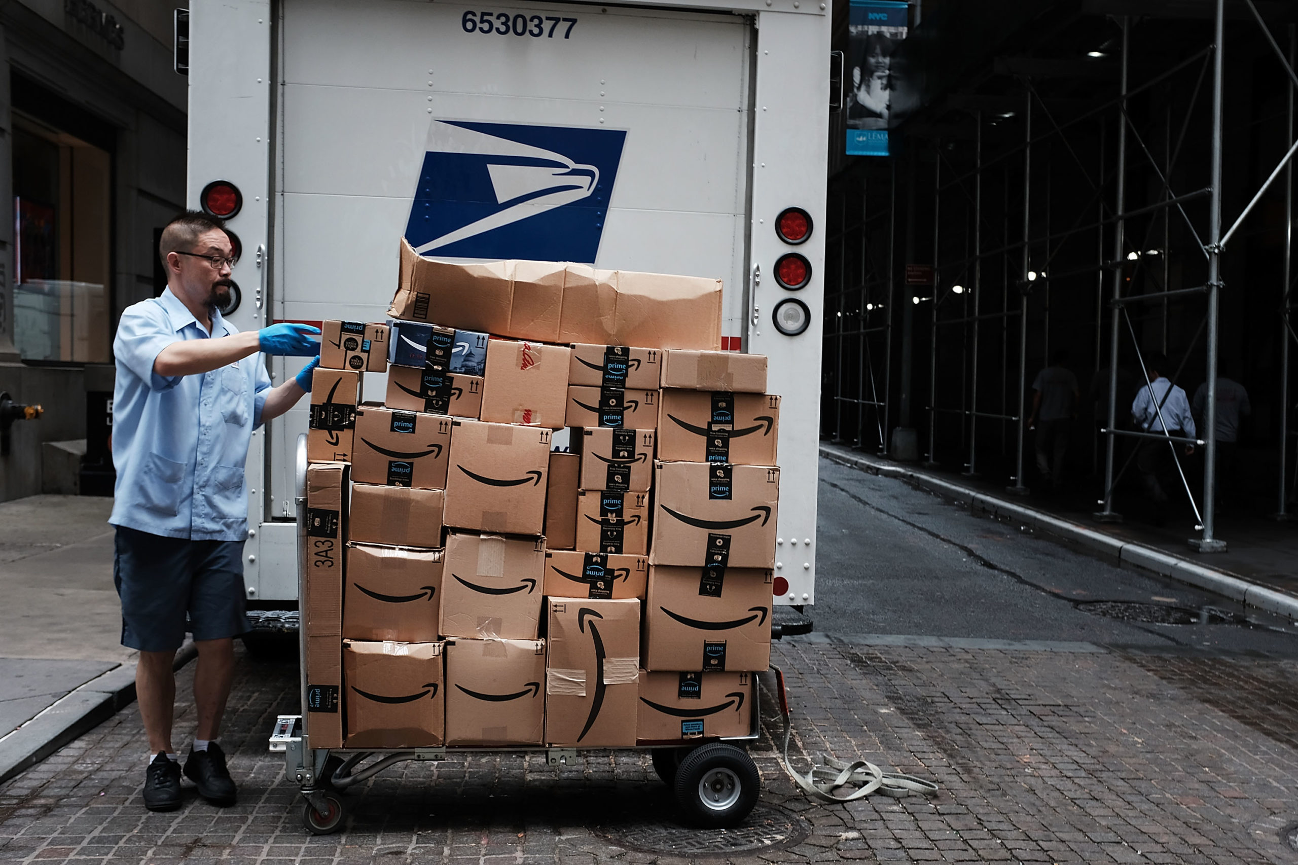 A postal worker delivers Amazon boxes outside of the New York Stock Exchange in New York City. (Spencer Platt/Getty Images)