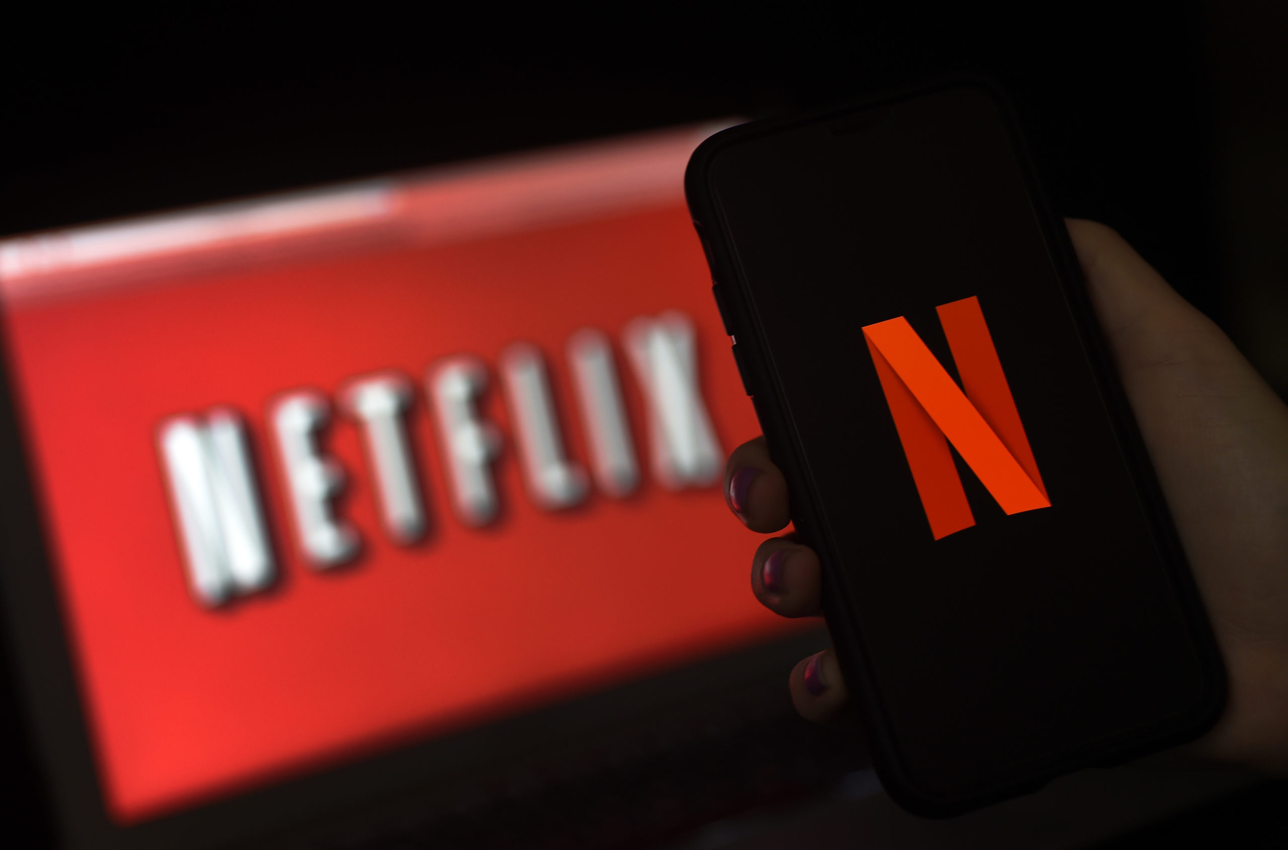 In this photo illustration a computer screen and mobile phone display the Netflix logo on March 31, 2020 in Arlington, Virginia. - According to Netflix chief content officer Ted Sarandos, Netflix viewership is on the rise during the coronavirus outbreak. (Photo by Olivier DOULIERY / AFP) (Photo by OLIVIER DOULIERY/AFP via Getty Images)