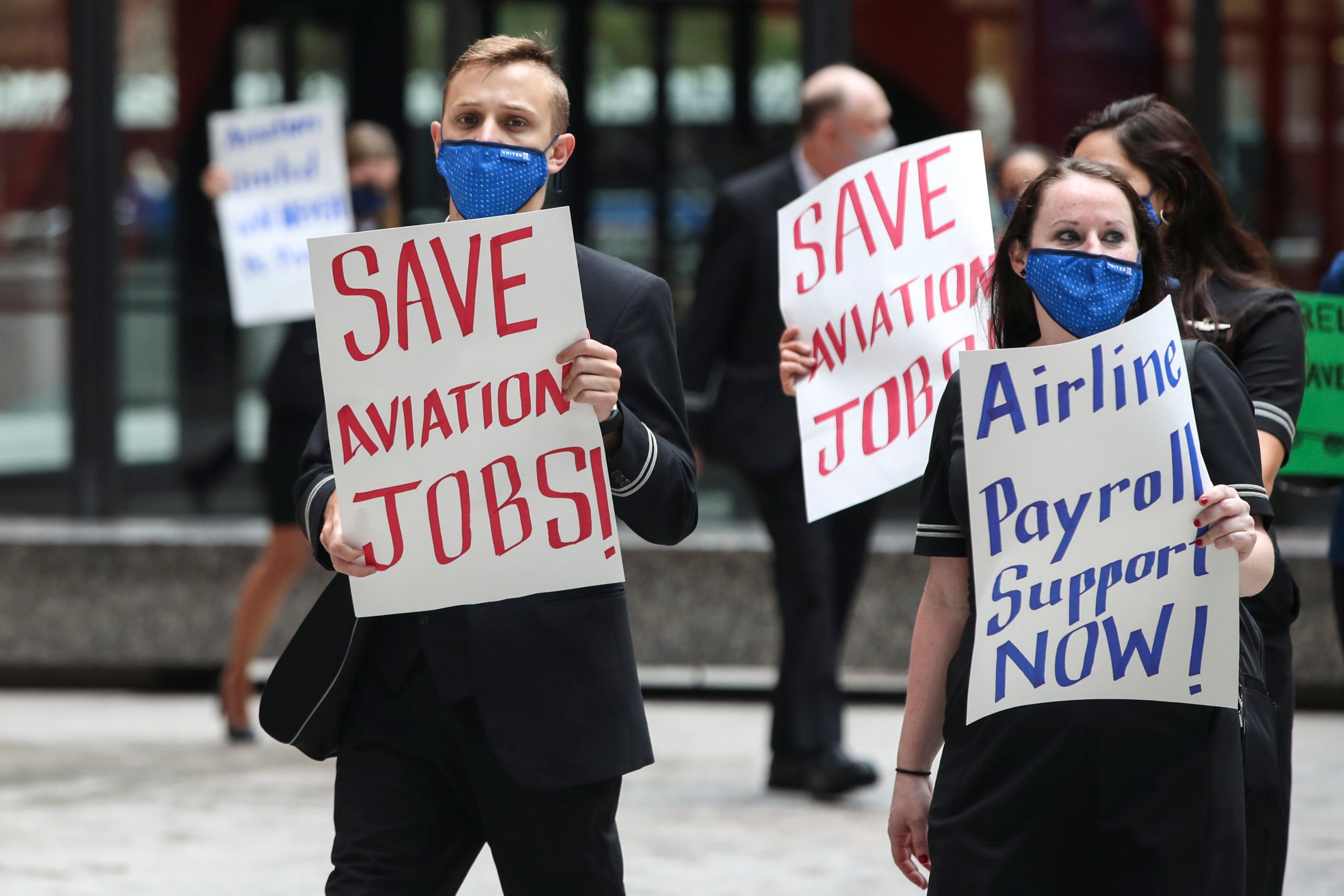 Airline industry workers hold signs during a protest in Chicago, Illinois on Sept. 9, 2020. (Kamil Krzaczynski/AFP via Getty Images)
