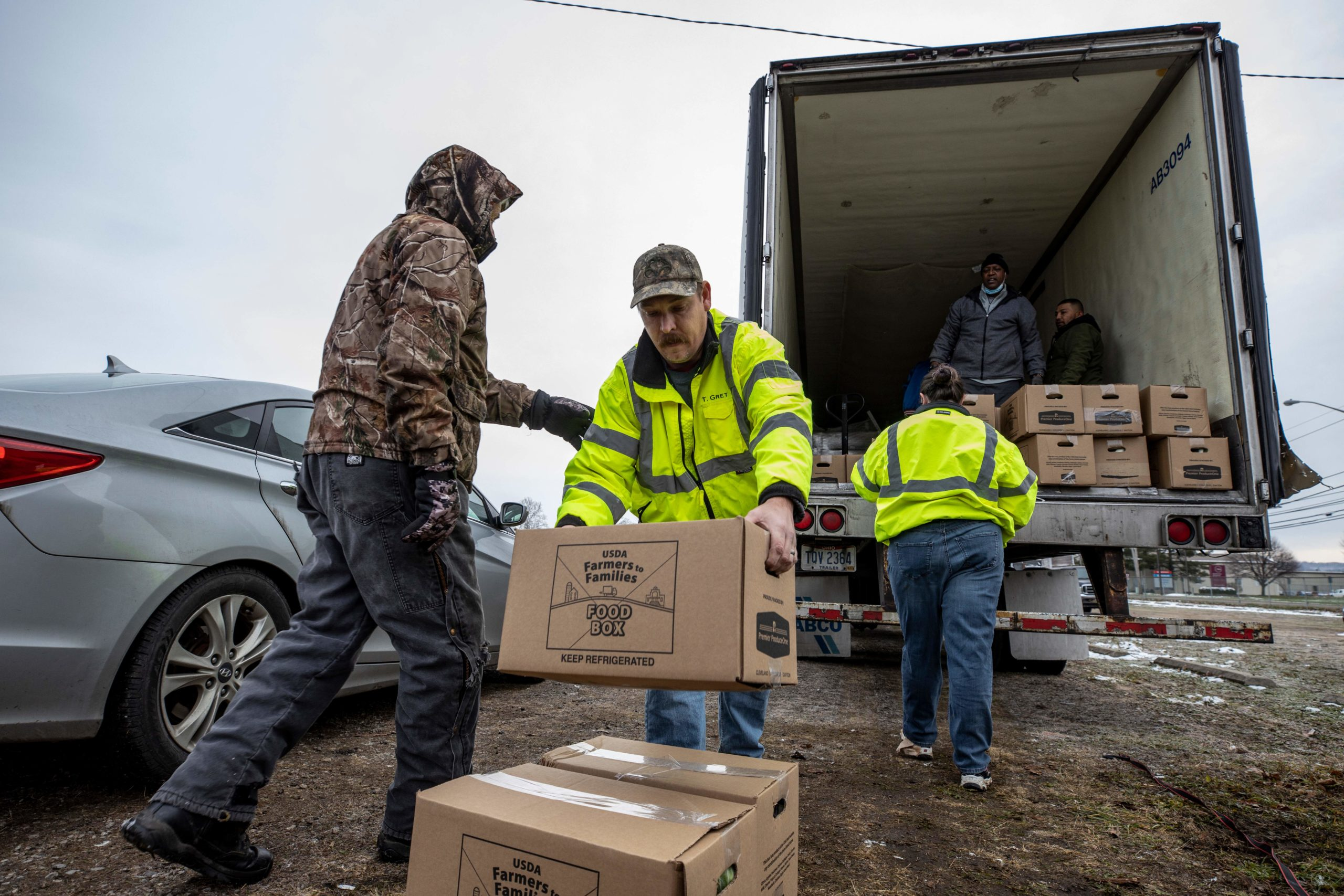 Volunteers work in an assembly line manner to unload a semi truck full of food boxes in Athens, Ohio in December. (Stephen Zenner/AFP via Getty Images)