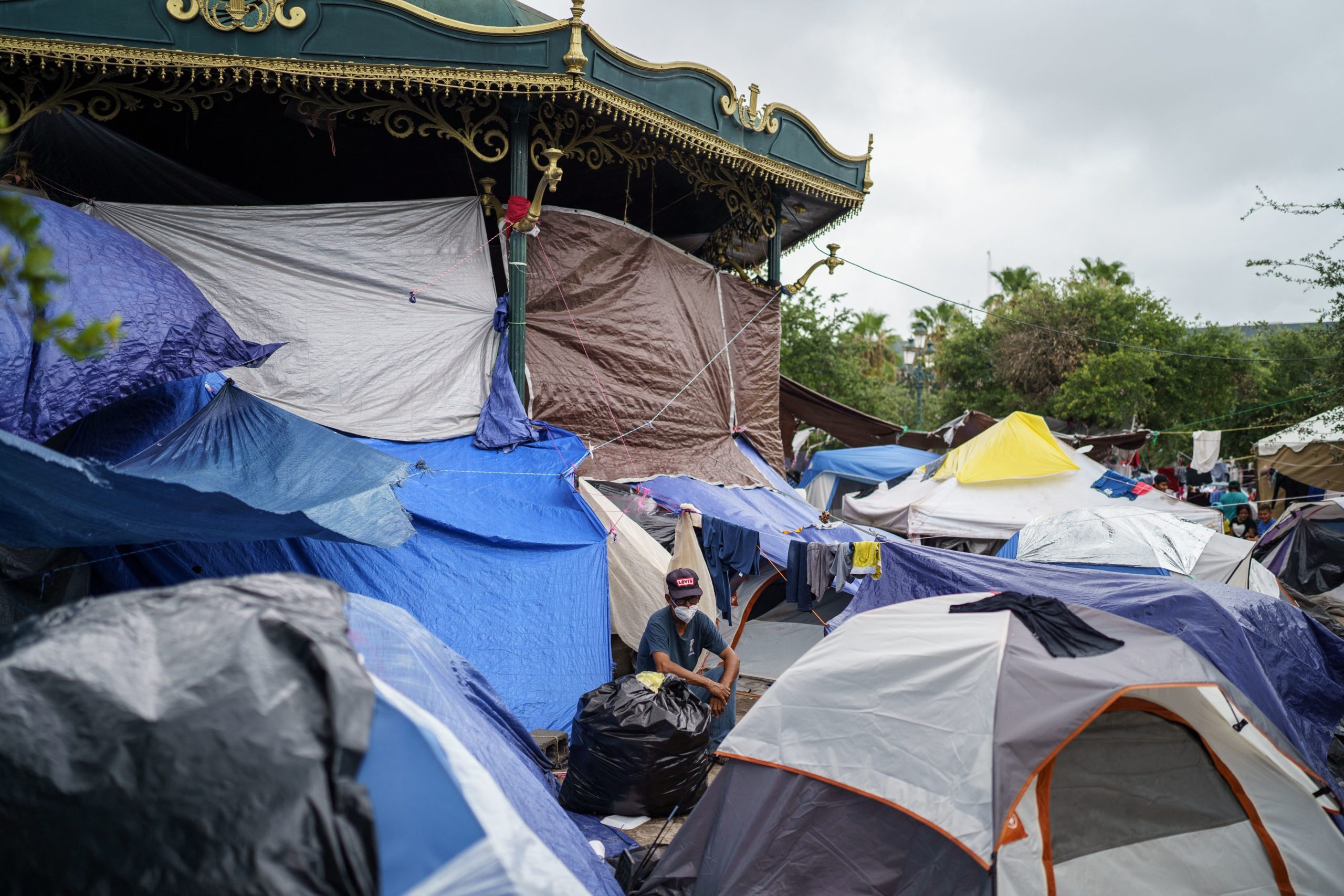 A man sits among a sea of tents in a makeshift migrant camp in the border town of Reynosa, Tamaulipas, Mexico on July 10, 2021. (Photo by PAUL RATJE/AFP via Getty Images)