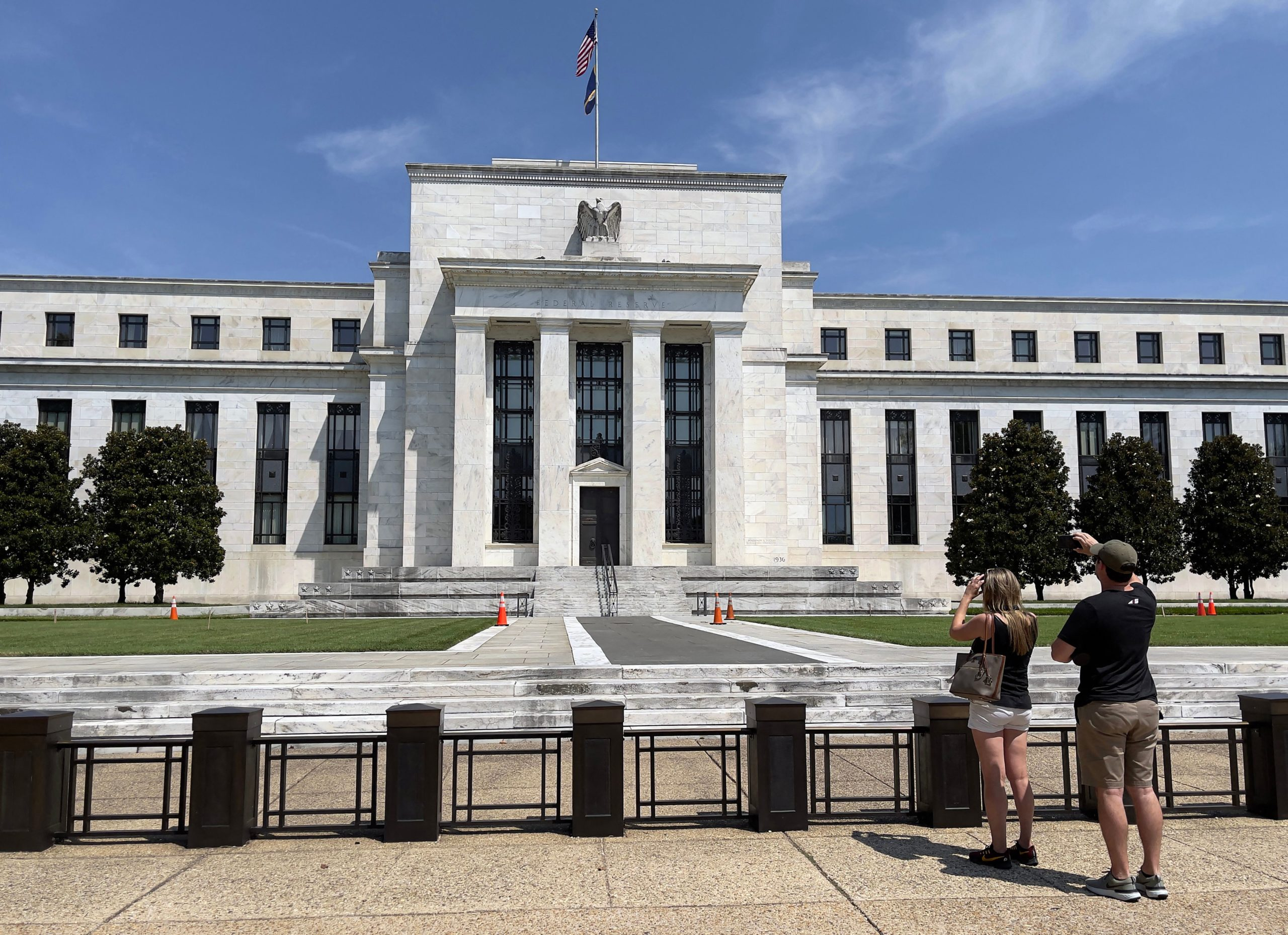 People take pictures of the Federal Reserve building in Washington, D.C. on Aug. 6. (Daniel Slim/AFP via Getty Images)