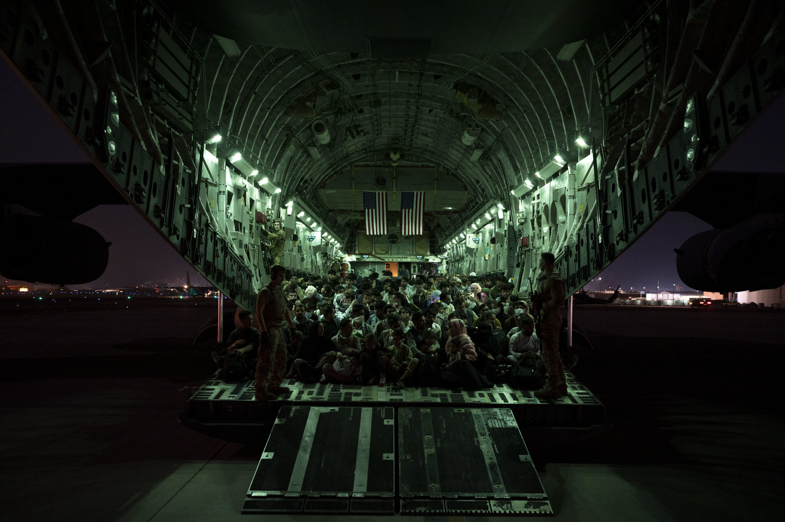 KABUL, AFGHANISTAN - AUGUST 21: In this handout provided by the U.S. Air Force, an air crew assigned to the 816th Expeditionary Airlift Squadron assists evacuees aboard a C-17 Globemaster III aircraft in support of the Afghanistan evacuation at Hamid Karzai International Airport on August 21, 2021 in Kabul, Afghanistan. (Photo by Taylor Crul/U.S. Air Force via Getty Images)