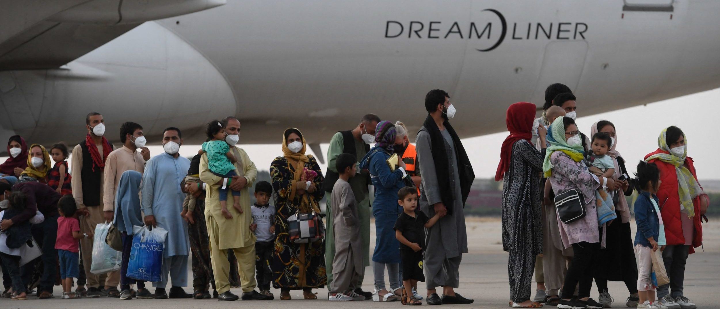 TOPSHOT - Refugees queue on the tarmac after disembarking from an evacuation flight from Kabul, at the Torrejon de Ardoz air base, 30 km from Madrid, on August 24, 2021. - Spain has been evacuating its nationals and local contractors from Afghanistan via Dubai since the Taliban swept to power ten days ago. Another 420 people are expected to arrive in Spain on August 24, 2021, including 290 people from Dubai and 130 who are expected to leave on a Spanish military plane from Kabul. (Photo by PIERRE-PHILIPPE MARCOU / AFP) (Photo by PIERRE-PHILIPPE MARCOU/AFP via Getty Images)