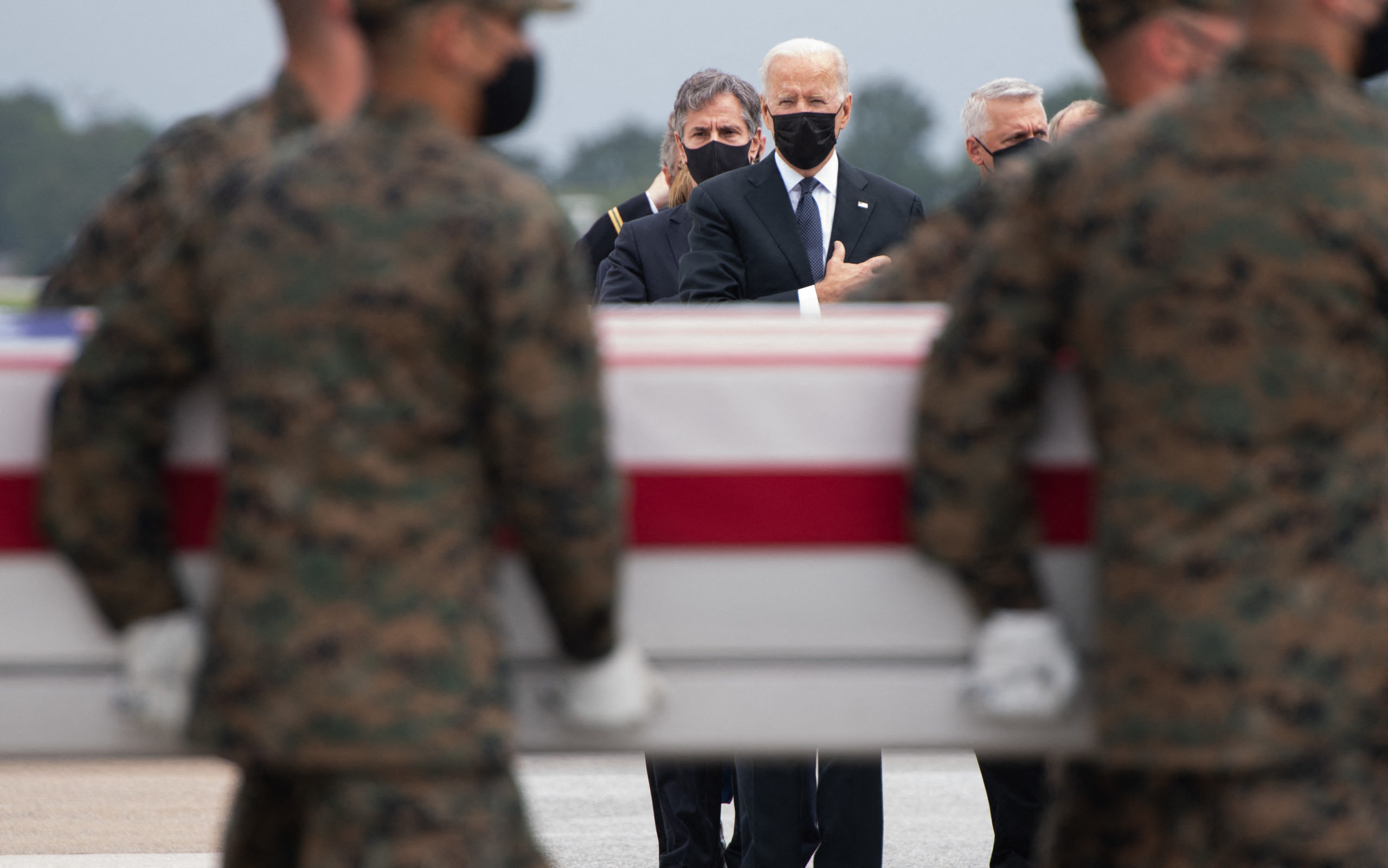 TOPSHOT - US President Joe Biden(C) attends the dignified transfer of the remains of fallen service members at Dover Air Force Base in Dover, Delaware, August, 29, 2021, after 13 members of the US military were killed in Afghanistan last week. - President Joe Biden prepared Sunday at a US military base to receive the remains of the 13 American service members killed in an attack in Kabul, a solemn ritual that comes amid fierce criticism of his handling of the Afghanistan crisis. Biden and his wife, Jill, both wearing black and with black face masks, first met far from the cameras with relatives of the dead in a special family center at Dover Air Force Base in Delaware.The base, on the US East Coast about two hours from Washington, is synonymous with the painful return of service members who have fallen in combat. (Photo by SAUL LOEB / AFP) (Photo by SAUL LOEB/AFP via Getty Images)