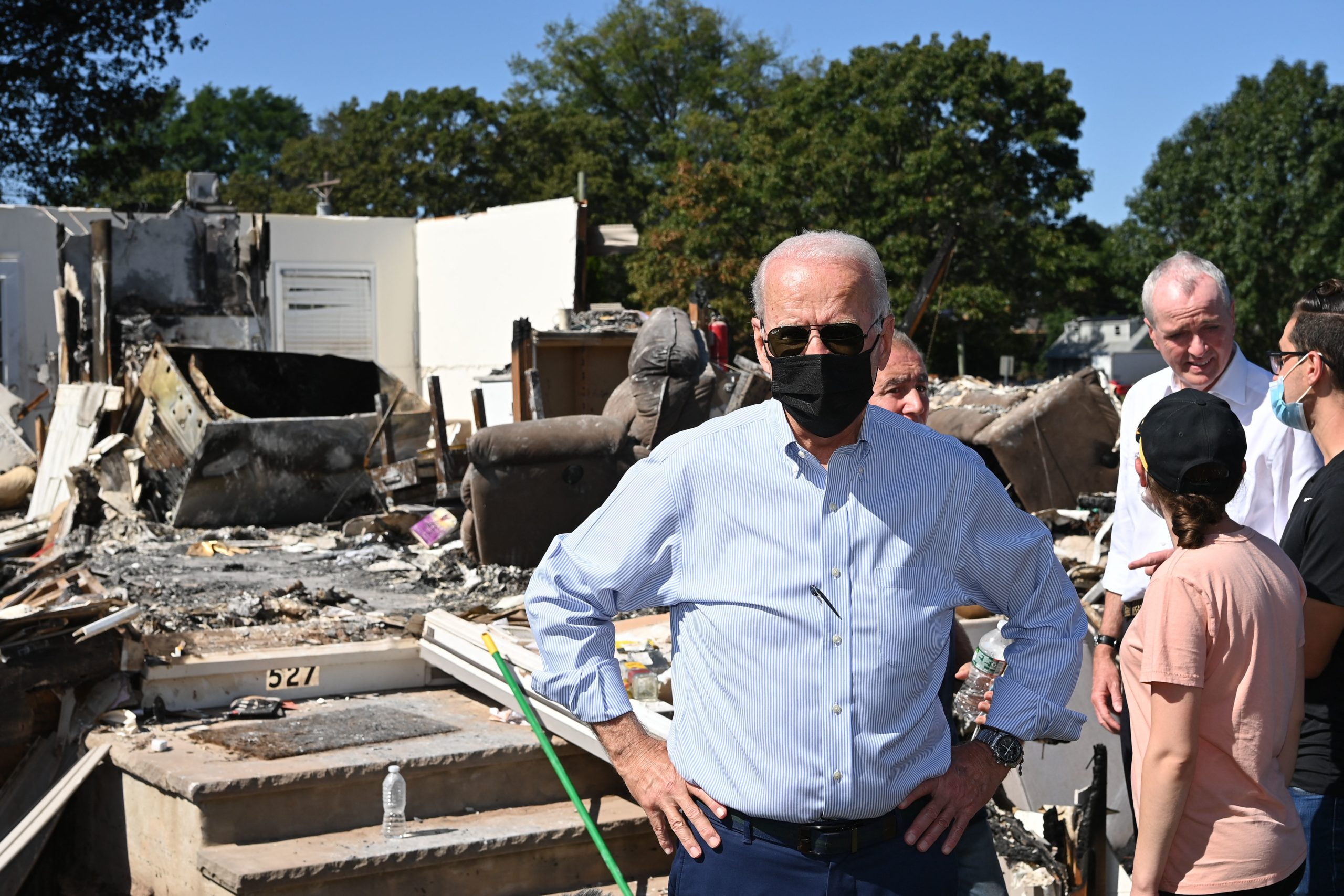 US President Joe Biden(C) tours a neighbourhood affected by Hurricane Ida in Manville, New Jersey on September 7, 2021. - President Joe Biden headed Tuesday to storm-ravaged New York and New Jersey, just days after inspecting the damage caused by Hurricane Ida in Louisiana. Biden -- who is pushing a giant infrastructure spending bill, including major funding for the green economy -- argues that extreme weather across the United States this summer is a harbinger of worse climate change to come. (Photo by MANDEL NGAN / AFP) (Photo by MANDEL NGAN/AFP via Getty Images)