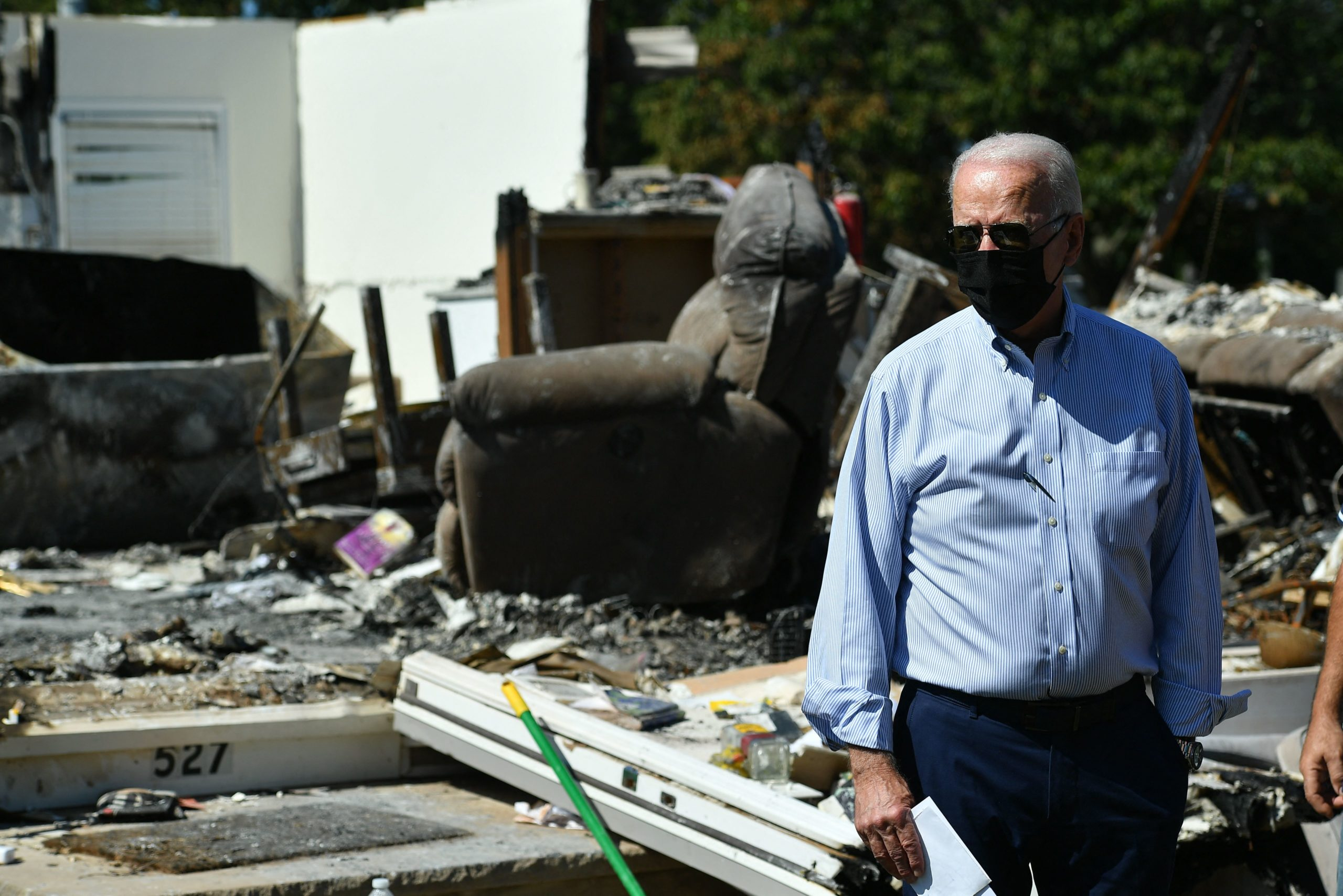 President Joe Biden tours a neighborhood affected by Hurricane Ida in Manville, New Jersey Tuesday. His budget and the infrastructure bill, include major funding for climate change mitigation measures as the country grapples with more frequent extreme weather. (MANDEL NGAN/AFP via Getty Images)
