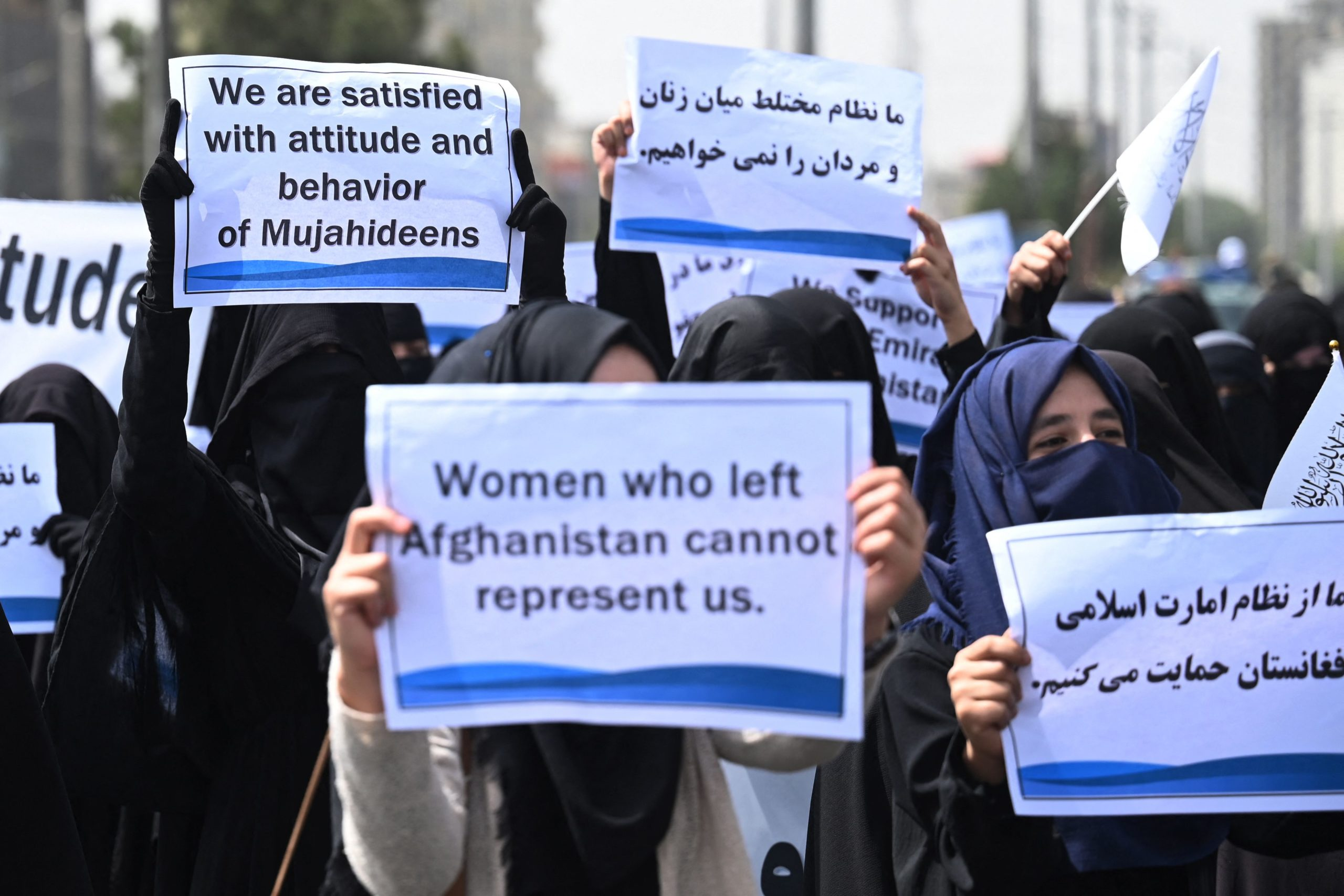Veiled women hold banners and placards while marching during a pro-Taliban rally outside the Shaheed Rabbani Education University in Kabul on September 11, 2021. (Photo by AAMIR QURESHI/AFP via Getty Images)