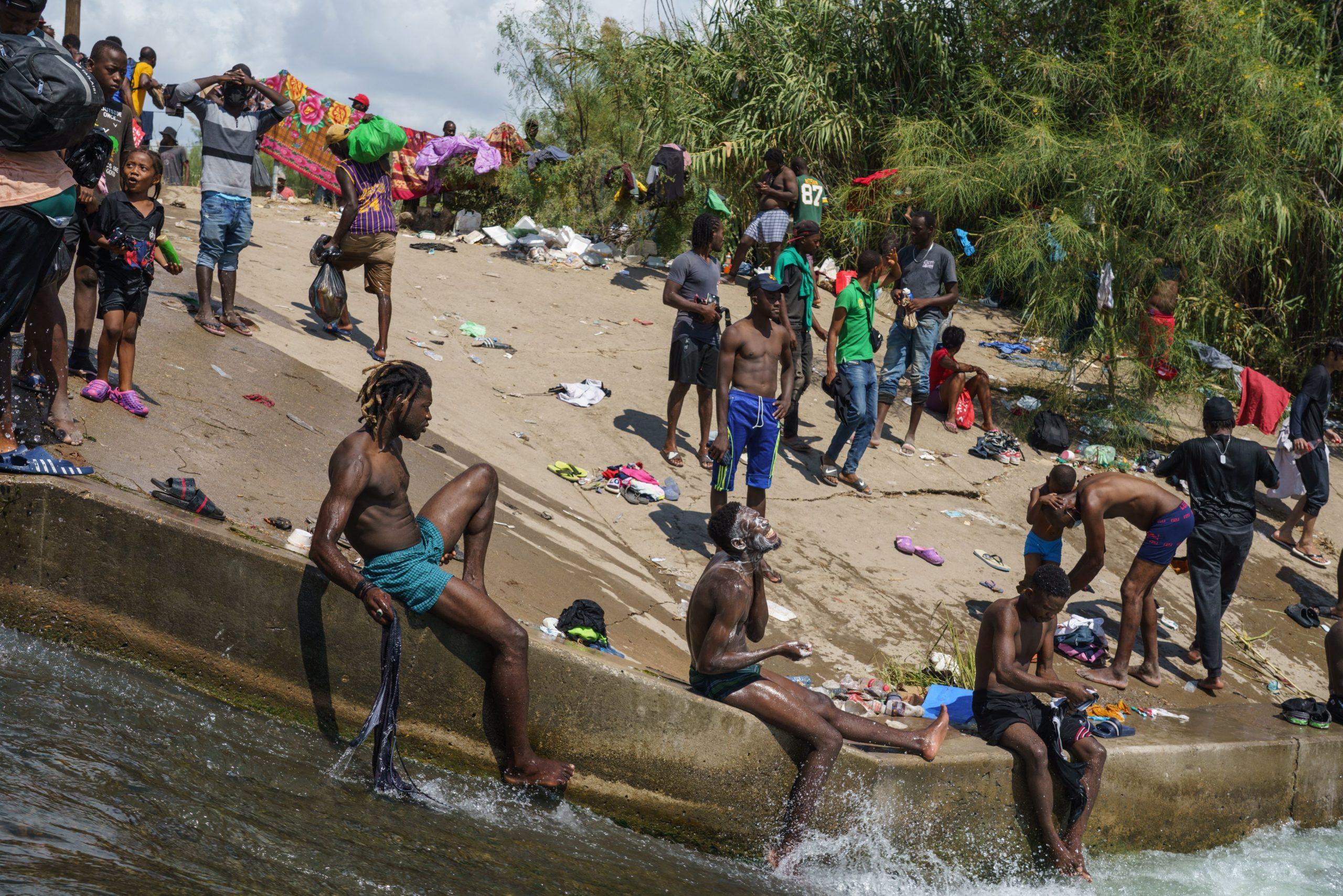 Migrant men bathe in the Rio Grande near the Del Rio-Acuna Port of Entry in Del Rio, Texas, on September 18, 2021. (Photo by PAUL RATJE/AFP via Getty Images)