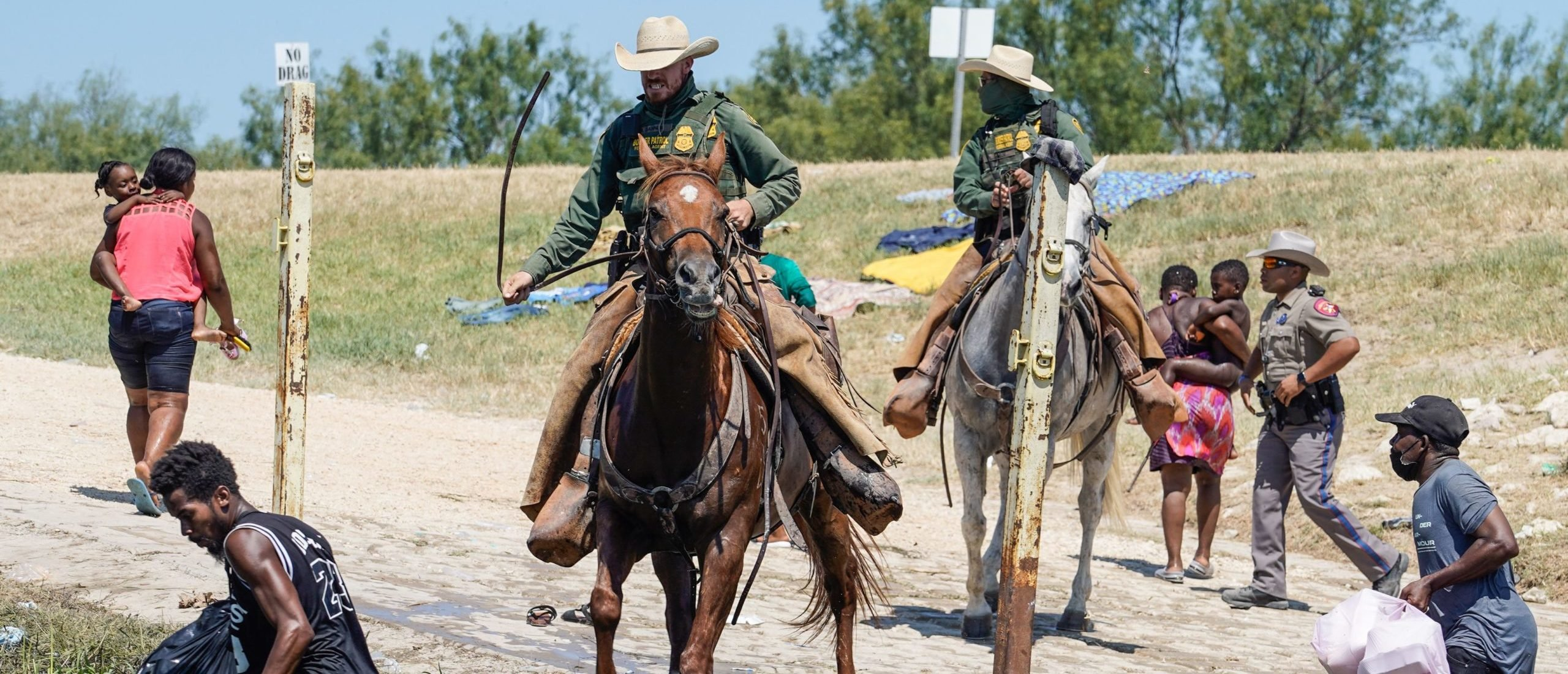 TOPSHOT - United States Border Patrol agents on horseback try to stop Haitian migrants from entering an encampment on the banks of the Rio Grande near the Acuna Del Rio International Bridge in Del Rio, Texas on September 19, 2021. - US law enforcement are attempting to close off crossing points along the Rio Grande river where migrants cross to get food and water, which is scarce in the encampment. The United States said Saturday it would ramp up deportation flights for thousands of migrants who flooded into the Texas border city of Del Rio, as authorities scramble to alleviate a burgeoning crisis for President Joe Biden's administration. (Photo by PAUL RATJE / AFP) (Photo by PAUL RATJE/AFP via Getty Images)
