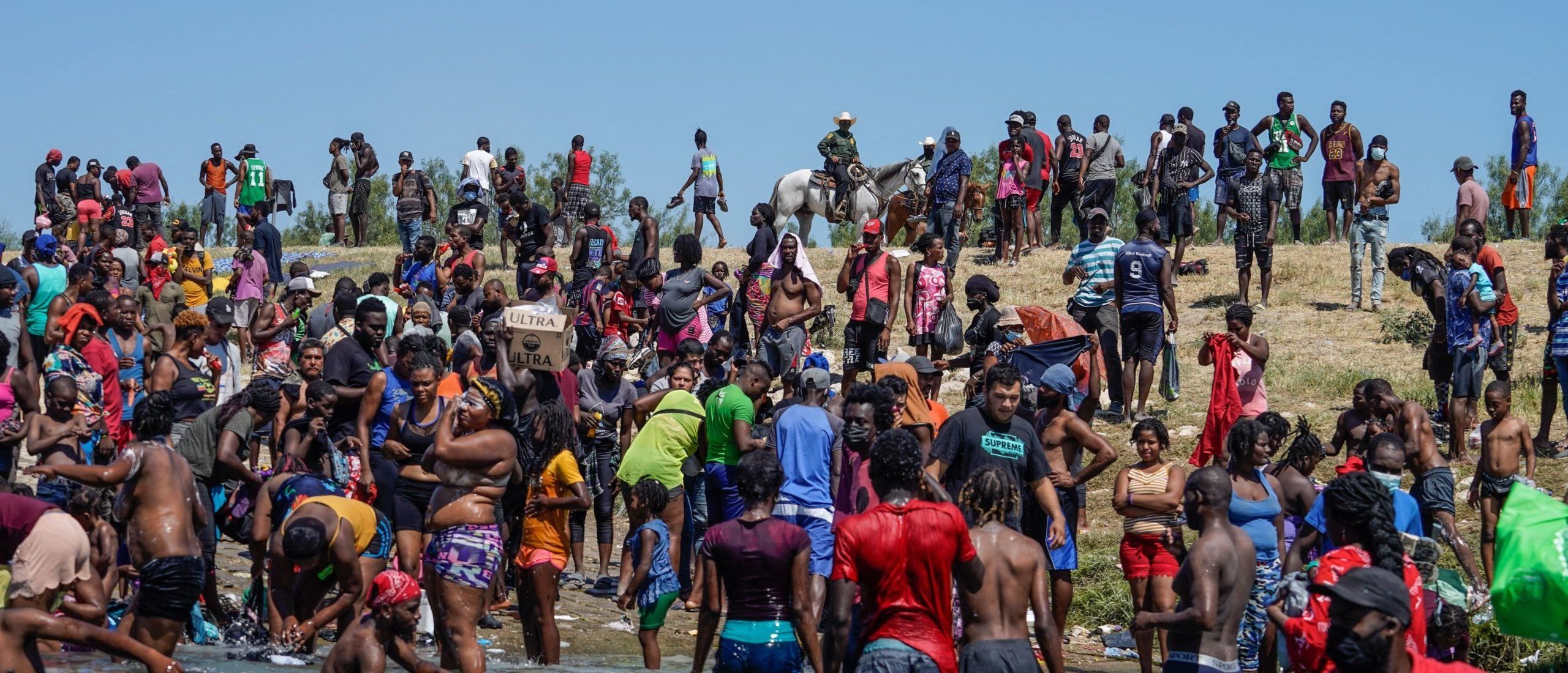 TOPSHOT - Haitian migrants, part of a group of over 10,000 people staying in an encampment on the US side of the border, cross the Rio Grande river to get food and water in Mexico, after another crossing point was closed near the Acuna Del Rio International Bridge in Del Rio, Texas on September 19, 2021. - The United States said Saturday it would ramp up deportation flights for thousands of migrants who flooded into the Texas border city of Del Rio, as authorities scramble to alleviate a burgeoning crisis for President Joe Biden's administration. (Photo by PAUL RATJE / AFP) (Photo by PAUL RATJE/AFP via Getty Images)