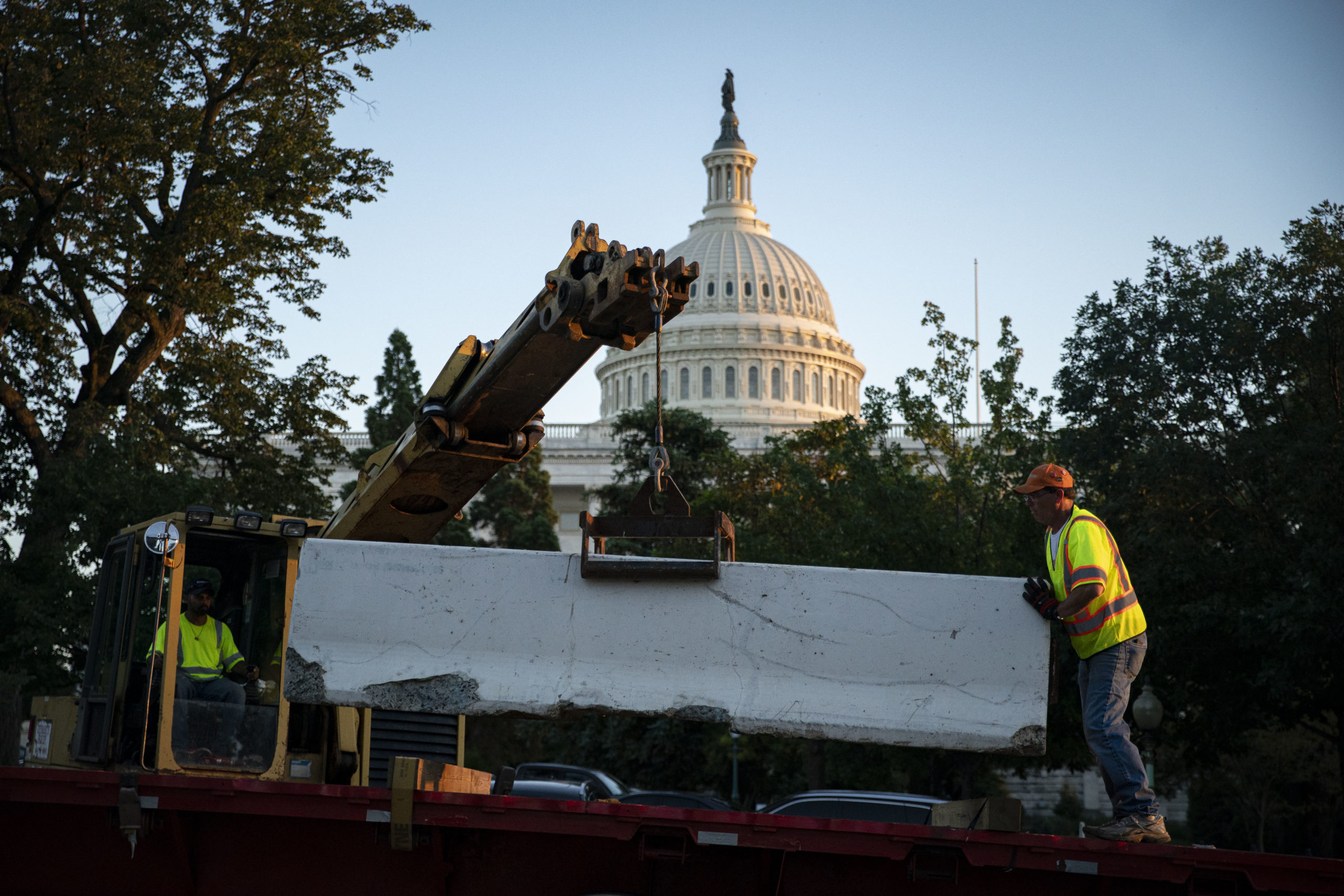 Workers remove security fencing surrounding the U.S. Capitol on Sunday. (Al Drago/Getty Images)