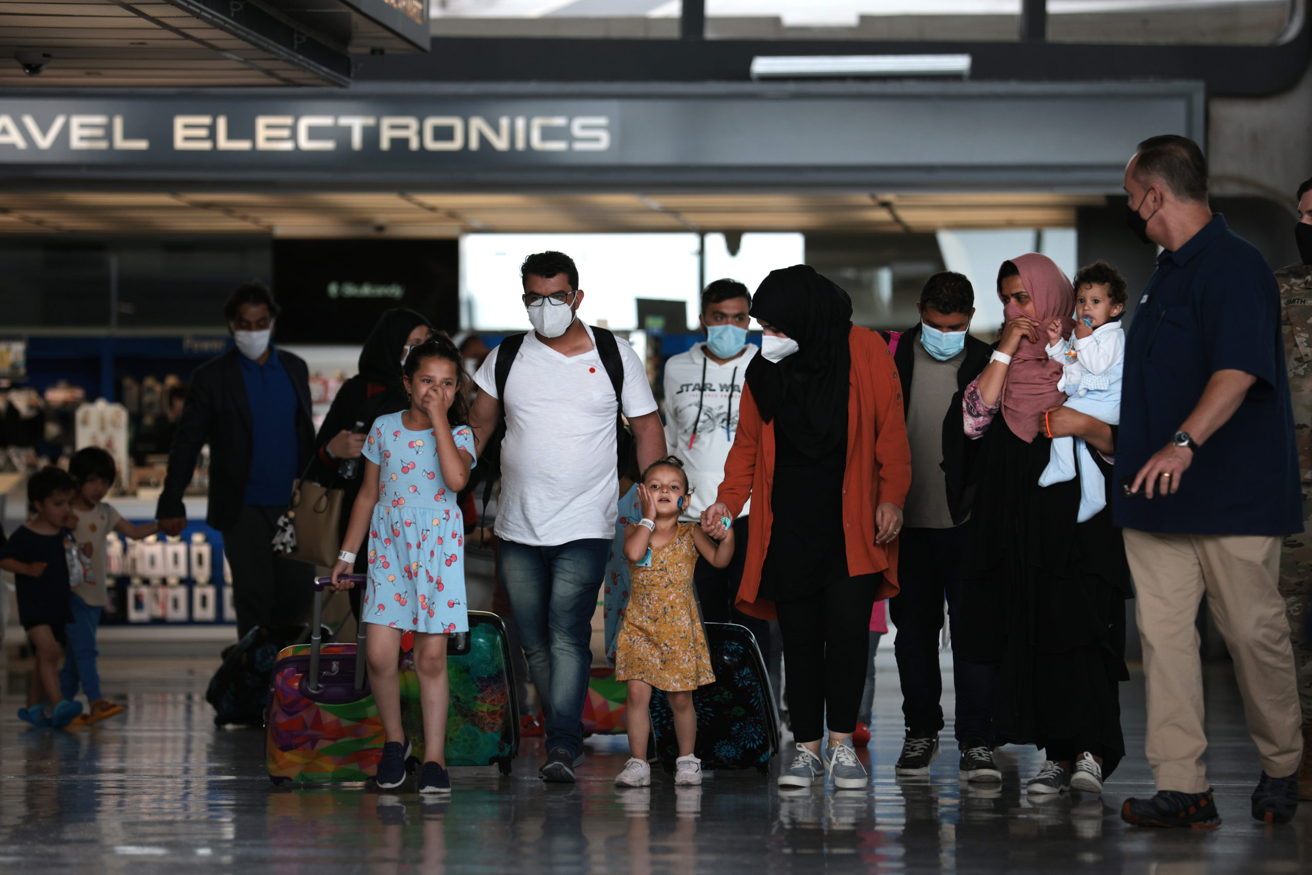 Refugees are led through the departure terminal to a bus at Dulles International Airport after being evacuated from Kabul following the Taliban takeover of Afghanistan on August 31, 2021 in Dulles, Virginia. (Photo by Anna Moneymaker/Getty Images)
