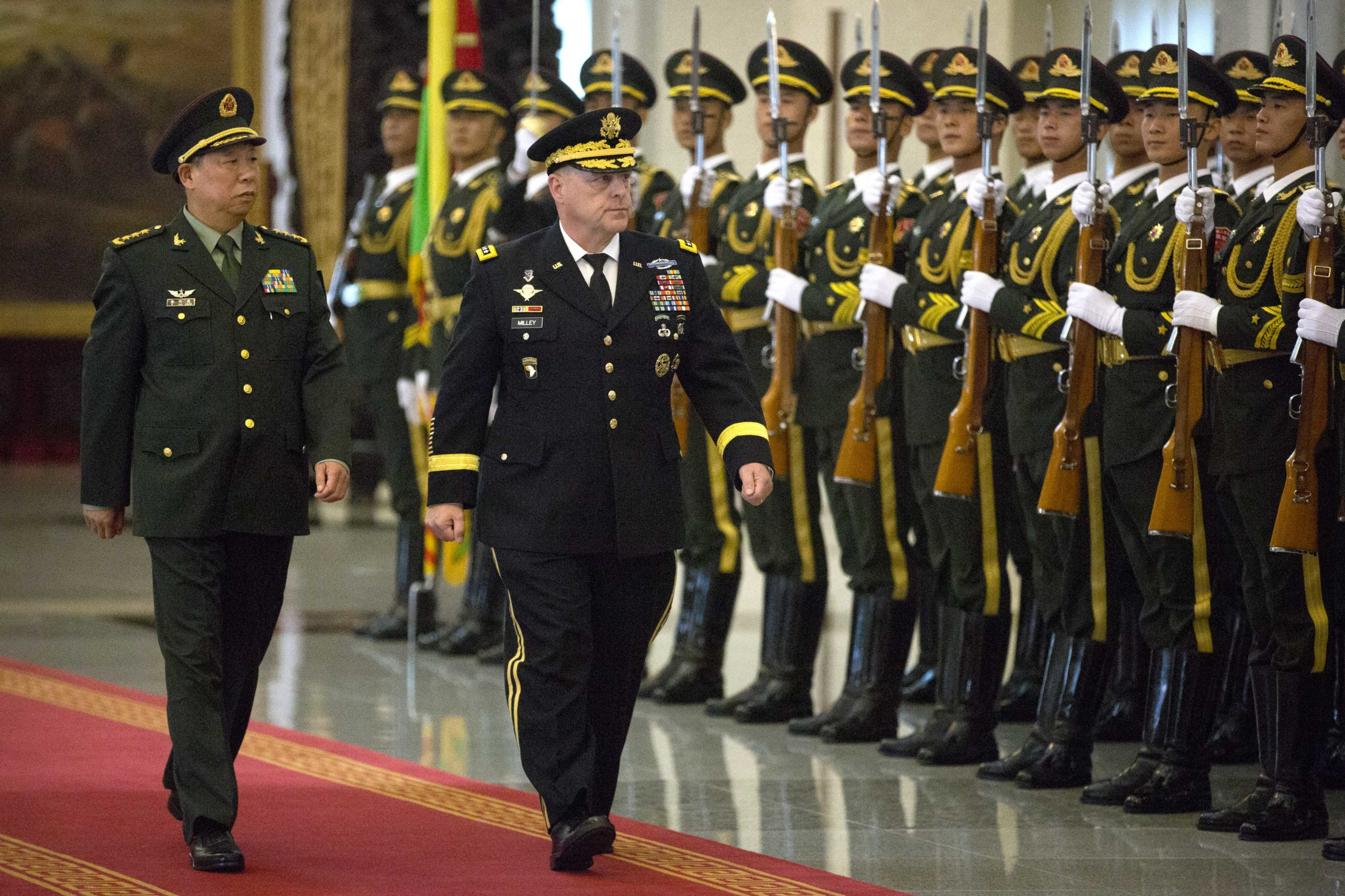 China's People's Liberation Army (PLA) General Li Zuocheng (L) and US Army Chief of Staff General Mark Milley (C) review an honour guard during a welcome ceremony at the Bayi Building in Beijing on August 16, 2016. / AFP / POOL / Mark Schiefelbein (Photo credit should read MARK SCHIEFELBEIN/AFP via Getty Images)