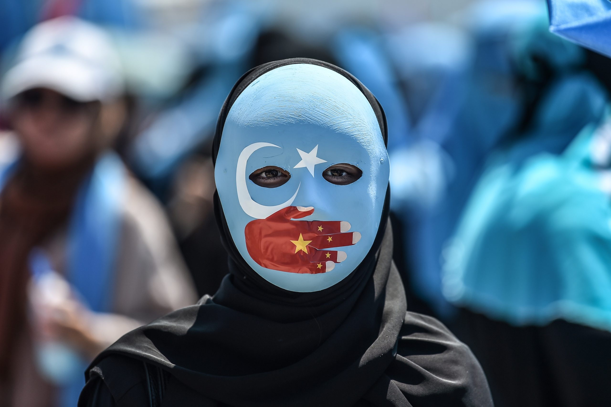 TOPSHOT - A demonstrator wearing a mask painted with the colours of the flag of East Turkestan and a hand bearing the colours of the Chinese flag attends a protest of supporters of the mostly Muslim Uighur minority and Turkish nationalists to denounce China's treatment of ethnic Uighur Muslims during a deadly riot in July 2009 in Urumqi, in front of the Chinese consulate in Istanbul, on July 5, 2018. - Nearly 200 people died during a series of violent riots that broke out on July 5, 2009 over several days in Urumqi, the capital city of the Xinjiang Uyghur Autonomous Region, in northwestern China, between Uyghurs and Han people. (Photo by OZAN KOSE / AFP) (Photo by OZAN KOSE/AFP via Getty Images)