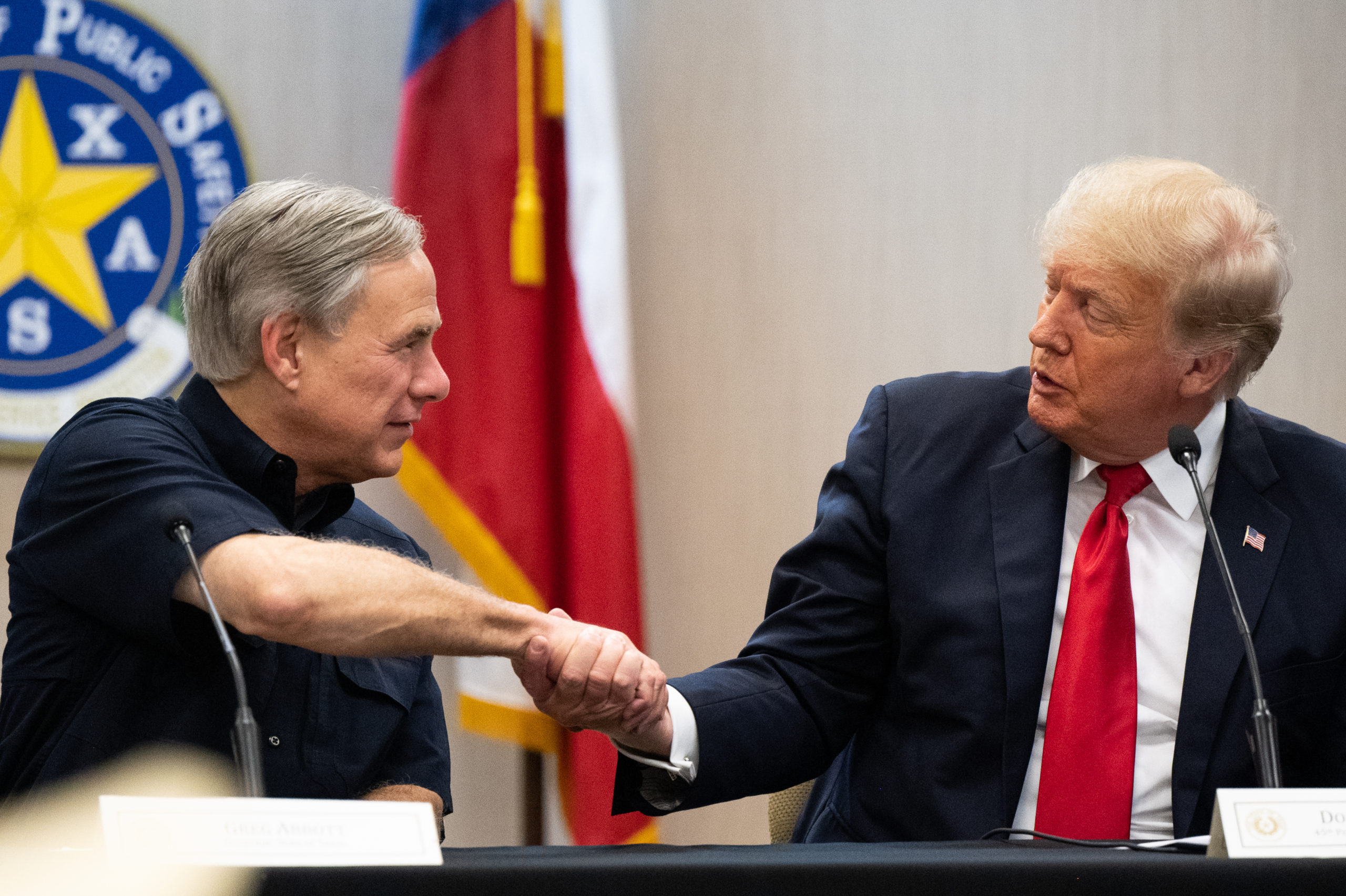 Texas Gov. Greg Abbott and former President Donald Trump shake hands during a border security briefing on June 30, 2021 in Weslaco, Texas. (Photo by Brandon Bell/Getty Images)