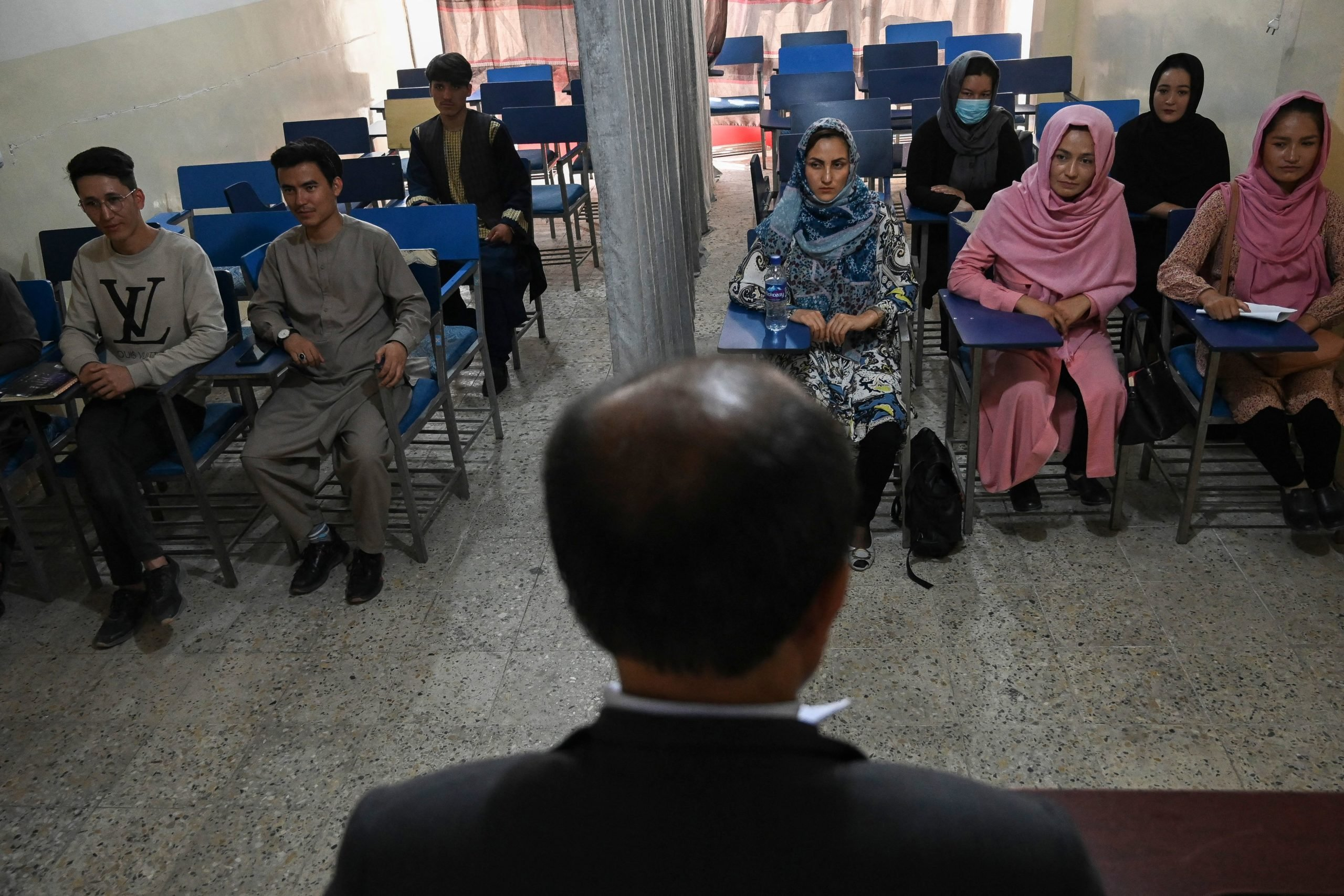 Students attend a class bifurcated by a curtain separating males and females at a private university in Kabul on September 7, 2021, to follow the Taliban's ruling. (Photo by AAMIR QURESHI/AFP via Getty Images)
