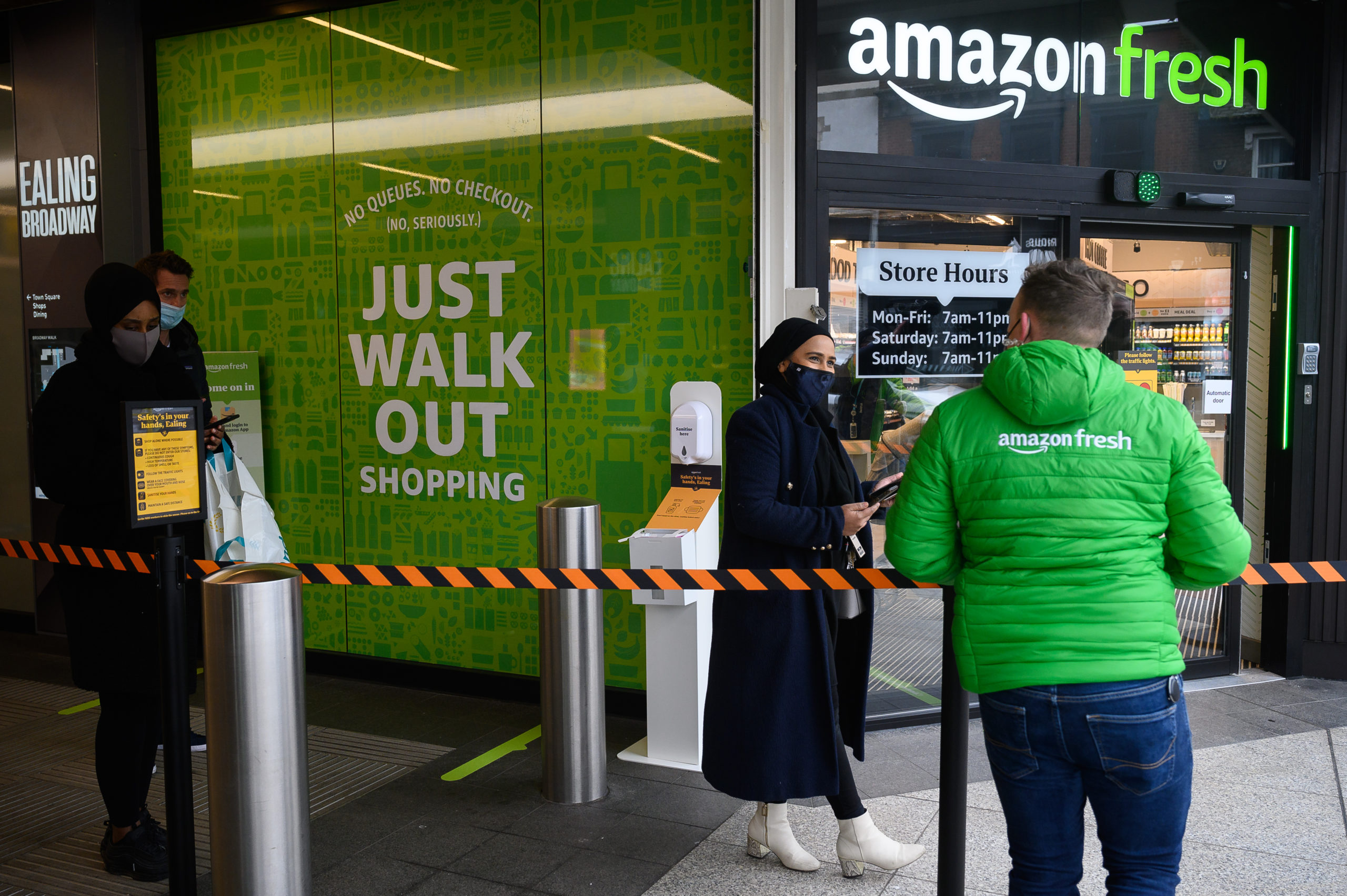 Members of staff assist customers as they wait to enter the UK's first branch of Amazon Fresh, on March 04, 2021, in the Ealing area of London, England. (Photo by Leon Neal/Getty Images)
