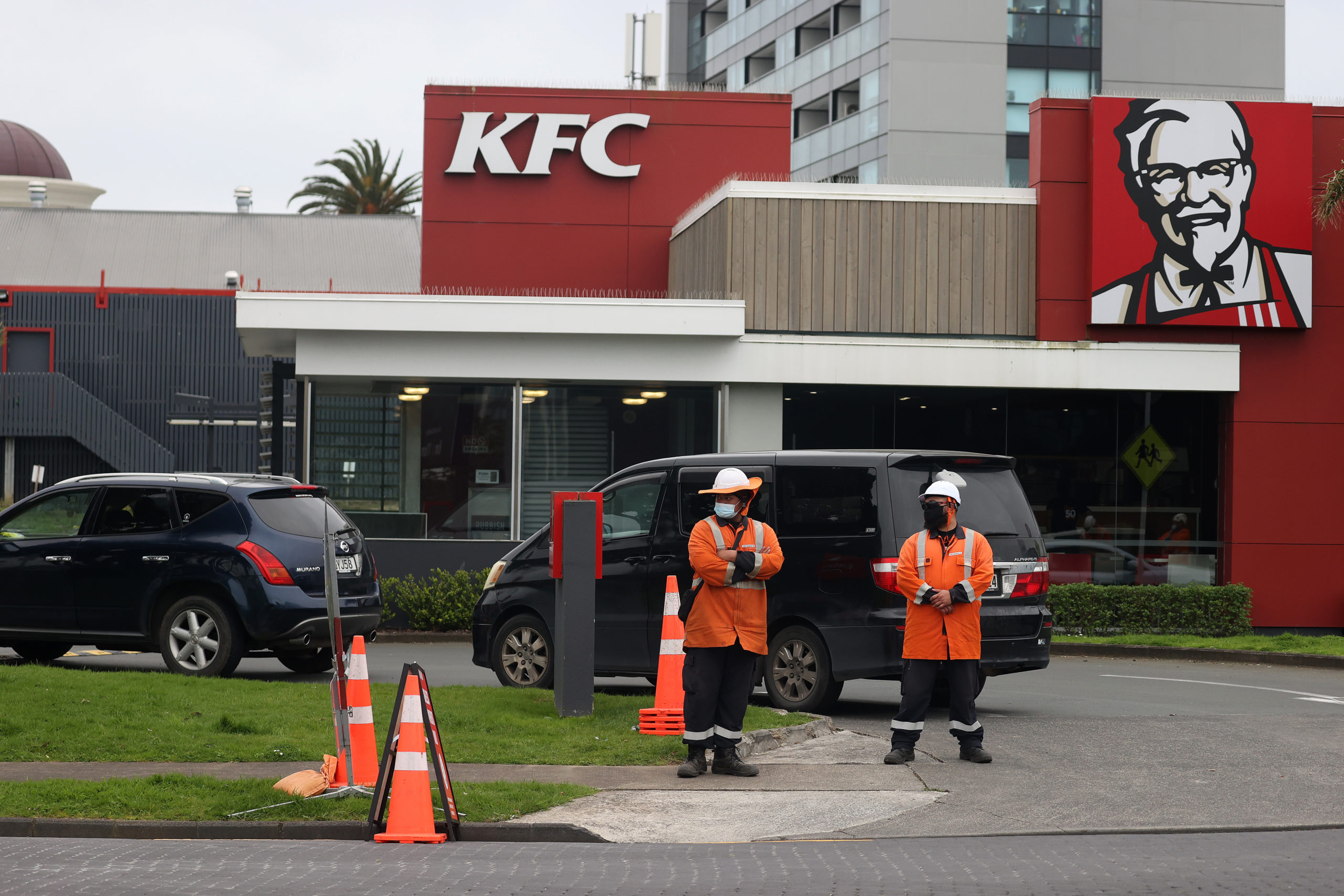 AUCKLAND, NEW ZEALAND - SEPTEMBER 22: Traffic management workers direct a large queue of cars through the KFC drive through in Manukau on September 22, 2021 in Auckland, New Zealand. Restrictions have eased for Auckland residents, with the Greater Auckland area moving to COVID-19 Alert Level 3 settings from 11:59pm on Tuesday. Under Alert Level 3 settings, essential businesses and services can operate but must ensure appropriate physical distancing and contact tracing, with early learning centres and schools to reopen for children up to Year 10 whose parents or caregivers need to return to work. Restaurants and cafes can reopen for takeaway, delivery or drive-through only. The only gatherings allowed under alert level 3 are weddings and civil union ceremonies, funerals and tangihanga, with up to 10 people only. People must remain in their household bubbles when not at work or school and masks remain mandatory outside of the home. (Photo by Phil Walter/Getty Images)