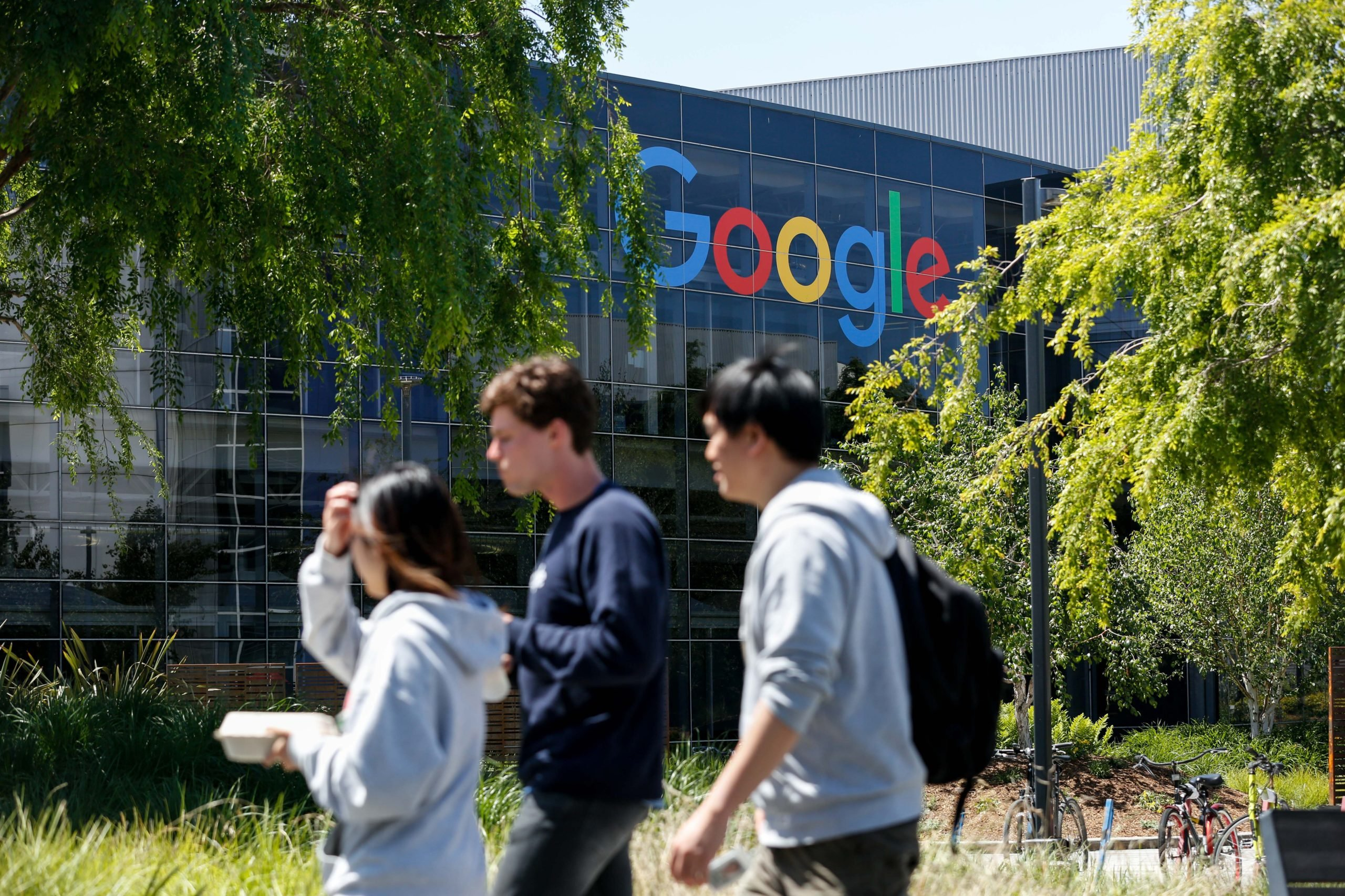 People walk in Google's main campus as a sit-in to protest against Google's retaliation against workers takes place within Google's main cafeteria in Mountain View, California on May 1, 2019. (Photo by Amy Osborne / AFP via Getty Images)