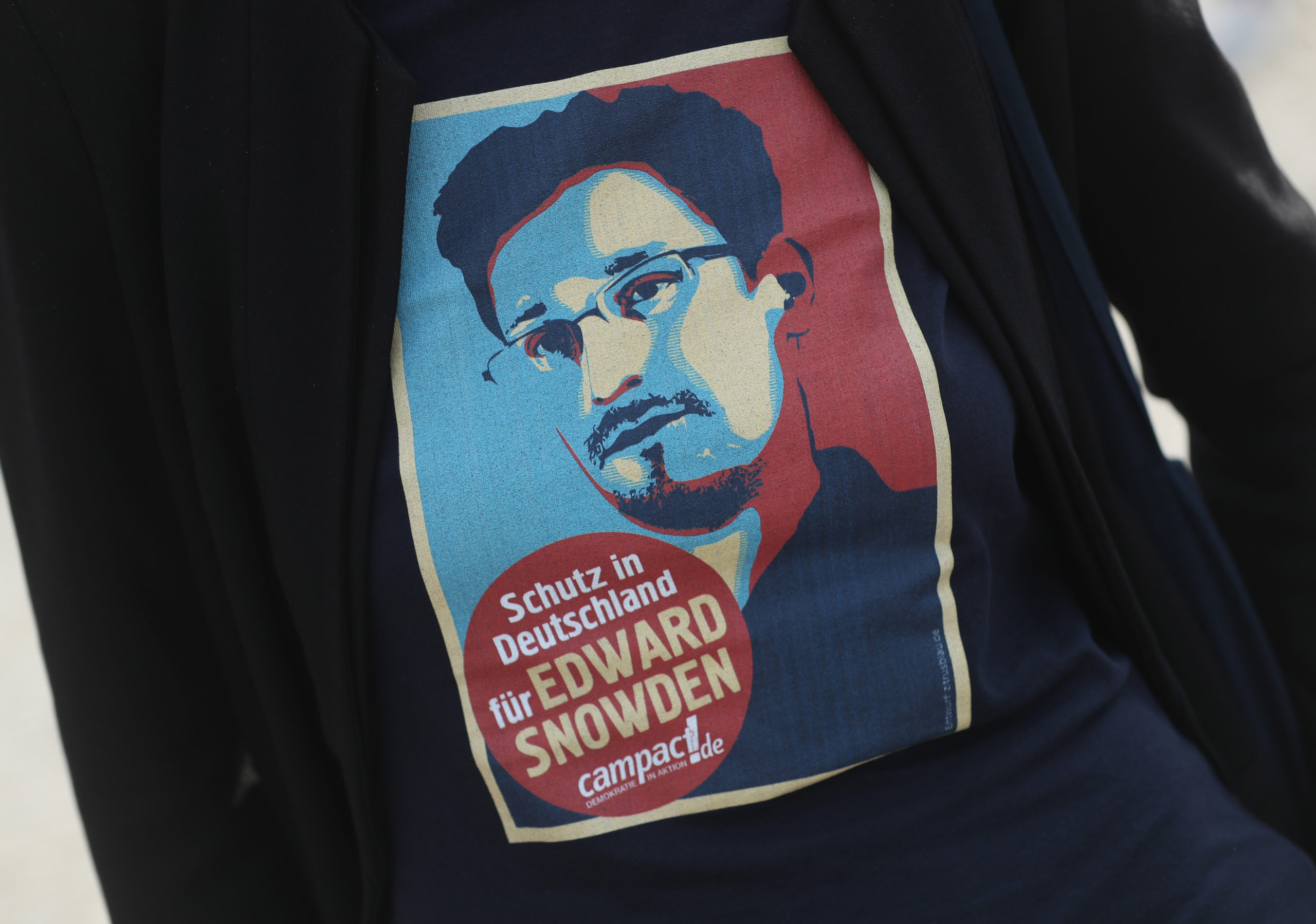 """Activists, including one wearing a t-shirt that shows a picture of U.S. whistleblower Edward Snowden that reads: """"Protection in Germany for Edward Snowden"""" protest against pending legislation they claim would greatly expand legal surveillance capabilities. (Photo by Sean Gallup/Getty Images)"""