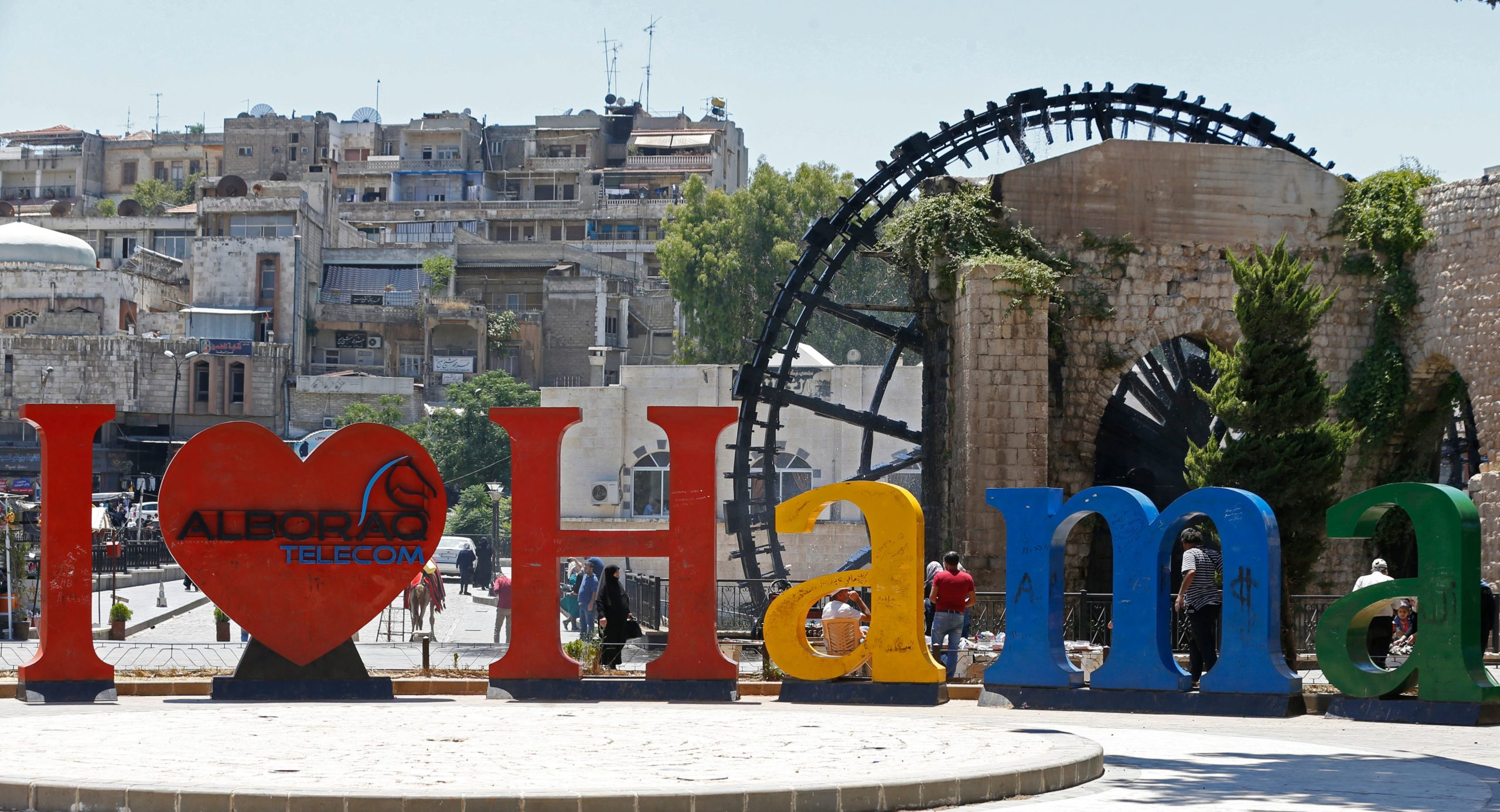 """This picture taken on June 24, 2020 shows a view of the """"I (love) Hama)"""" sculpture before the Jesrieh Noria (water wheel) along the Orontes (Assi) river in the city of Hama in west-central Syria. (Photo by LOUAI BESHARA/AFP via Getty Images)"""