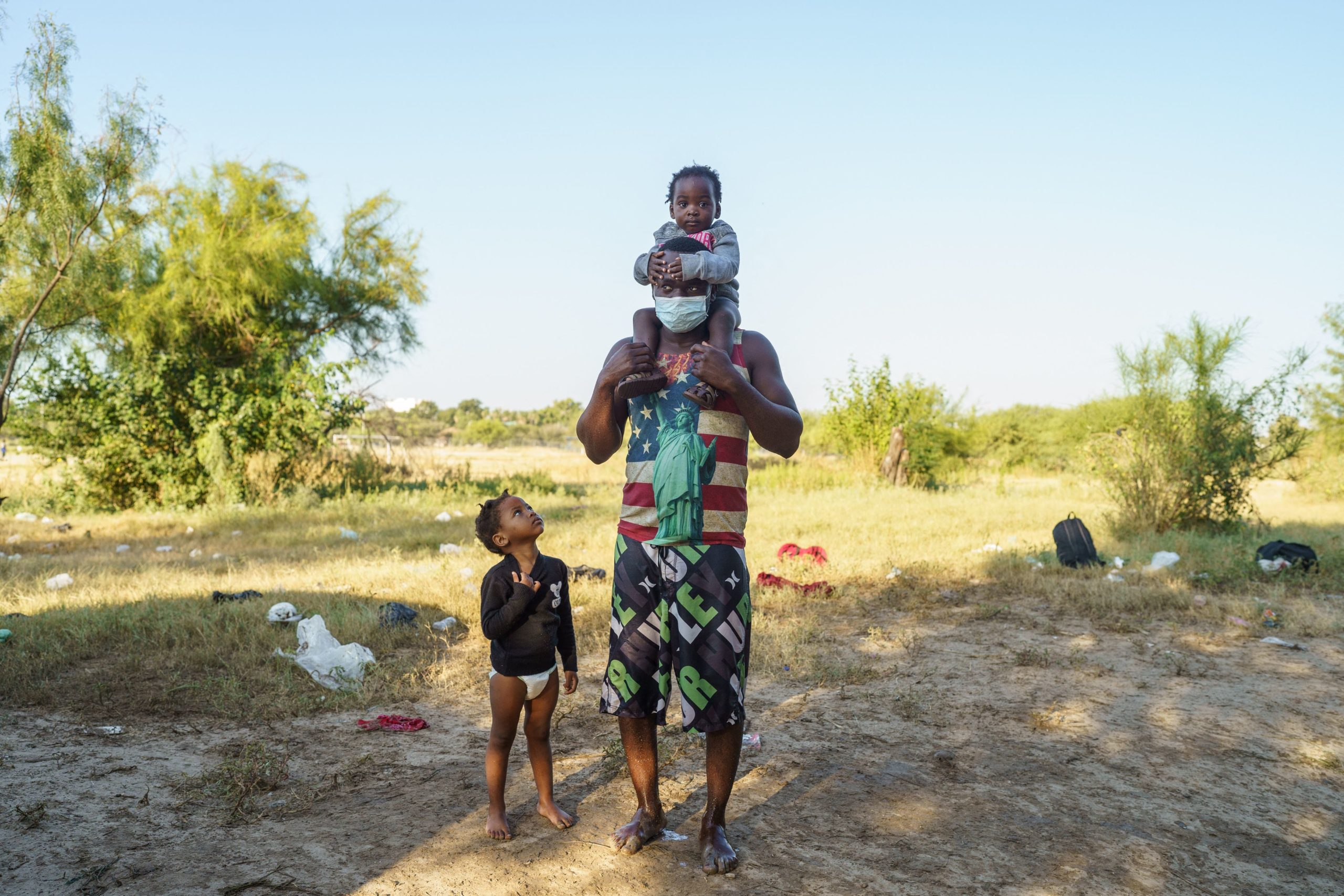 Ricardo, 31, from Haiti, holds his daughter Ricardini, 2, on his shoulders as another girl looks on, after they crossed the US-Mexico border, abandoning their goal of entering the United States in Ciudad Acuna, Coahuila state, Mexico on September 20, 2021. (Photo by PAUL RATJE/AFP via Getty Images)