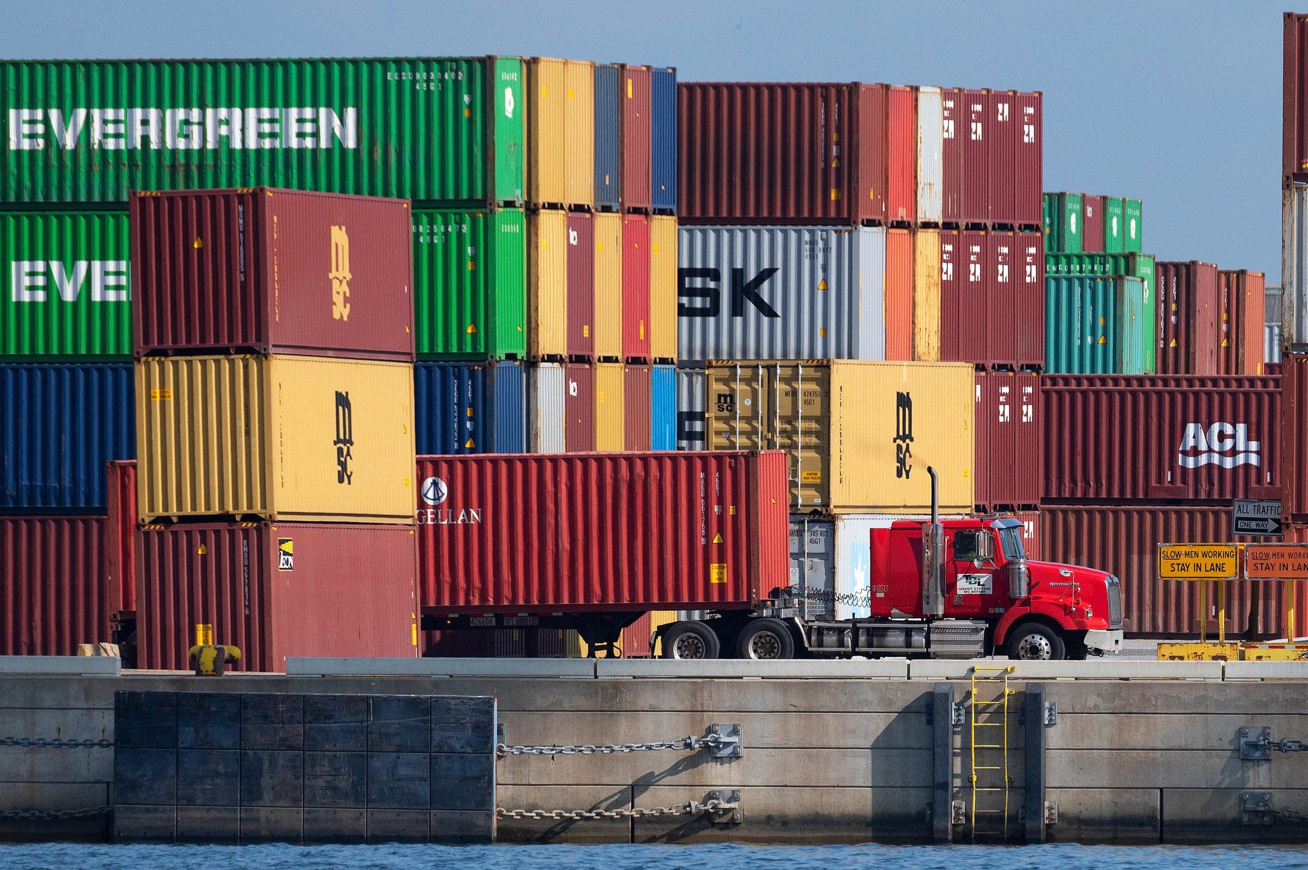 A truck driver passes stacked cargo containers at the Port of Baltimore in Baltimore, Maryland, on October 14, 2021. - Closed factories, clogged ports, no truck drivers -- up and down the global supply chain there are problems, raising concerns that it could disrupt the global economic recovery. (Photo by Jim WATSON / AFP) (Photo by JIM WATSON/AFP via Getty Images)