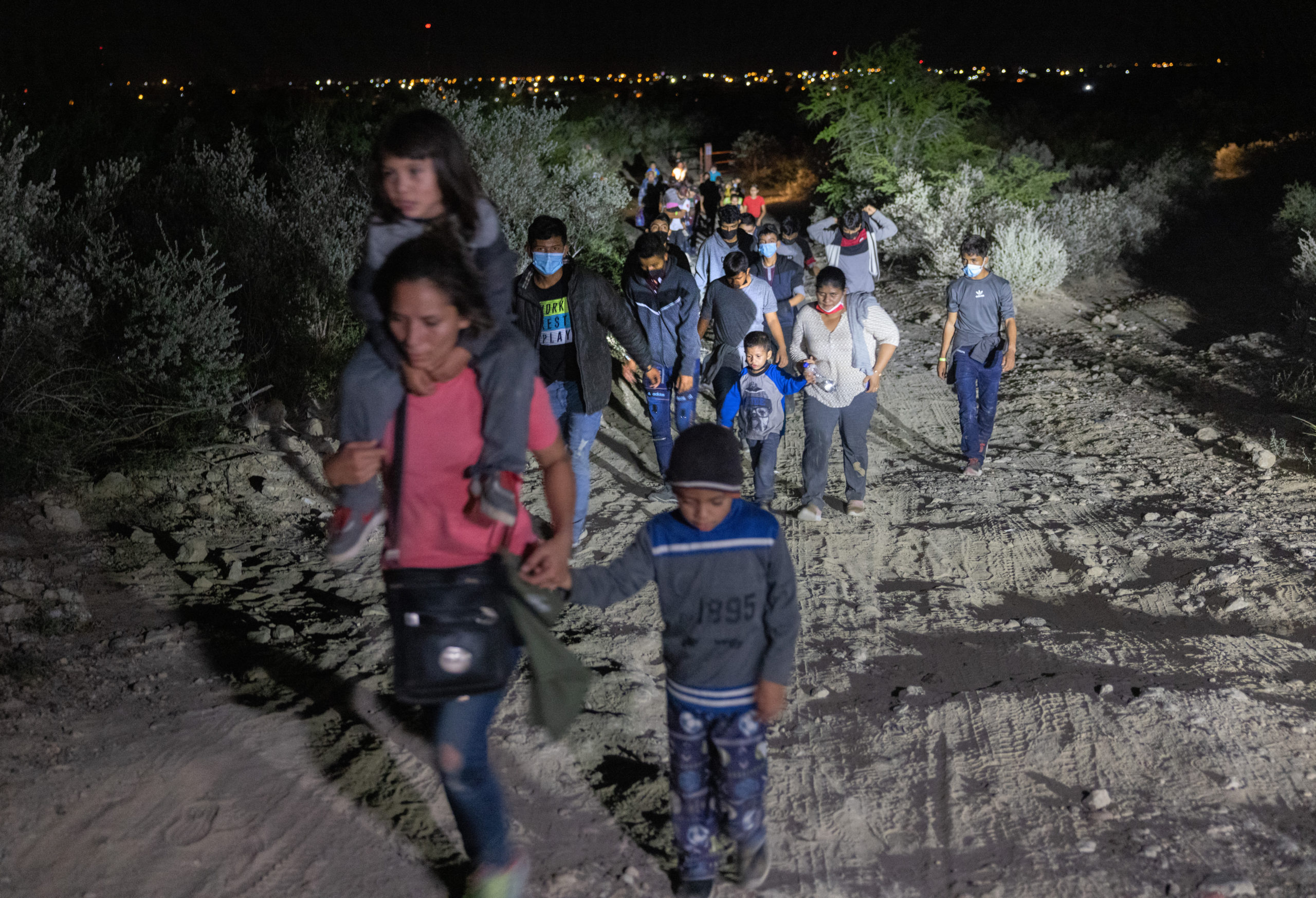 Immigrants walk towards a U.S. border checkpoint after they crossed the Rio Grande from Mexico on Aug. 14 in Roma, Texas. (John Moore/Getty Images)