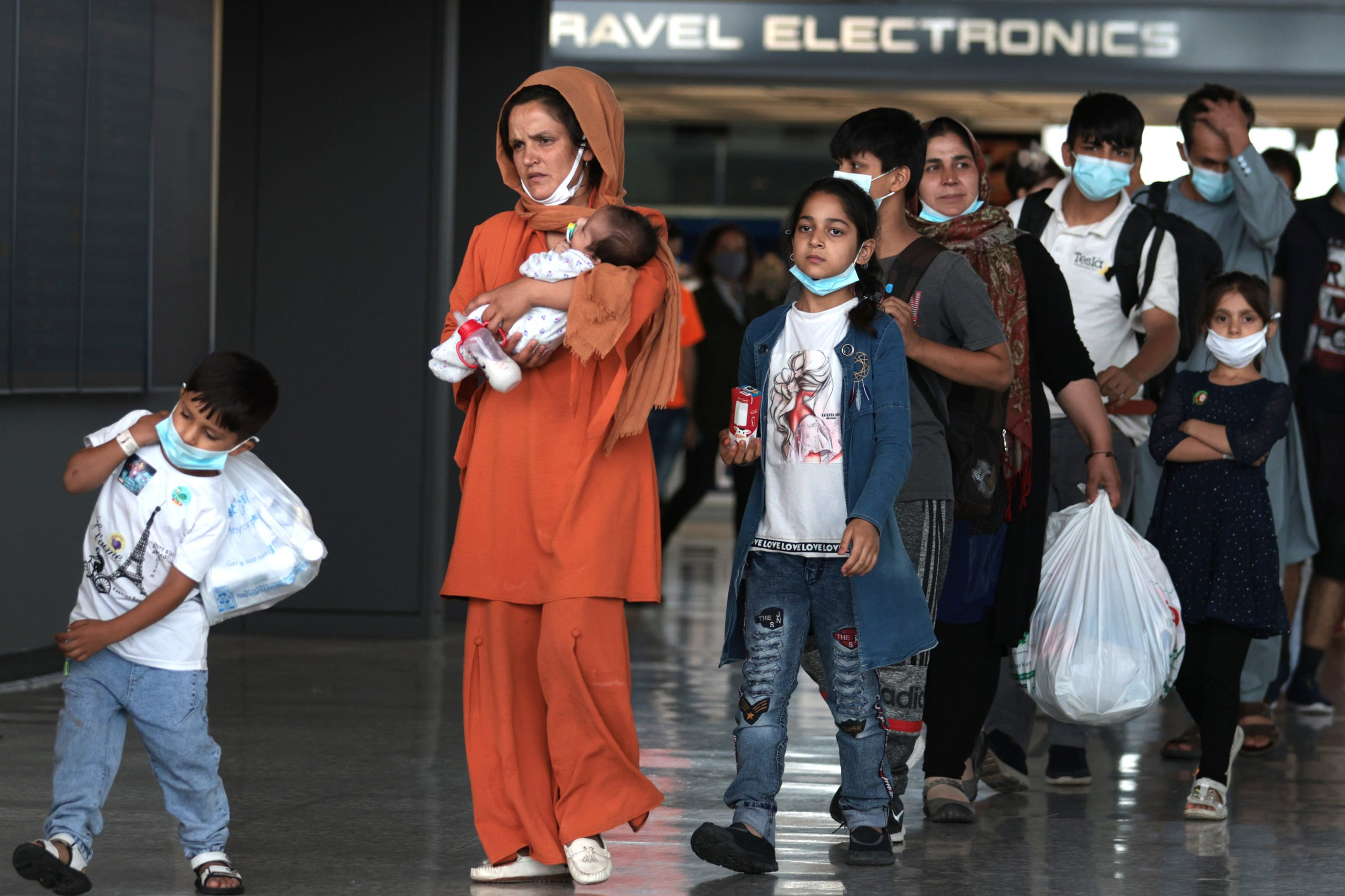 Refugees walk through the departure terminal to a bus at Dulles International Airport after being evacuated from Kabul following the Taliban takeover of Afghanistan on August 31, 2021 in Dulles, Virginia. (Photo by Anna Moneymaker/Getty Images)