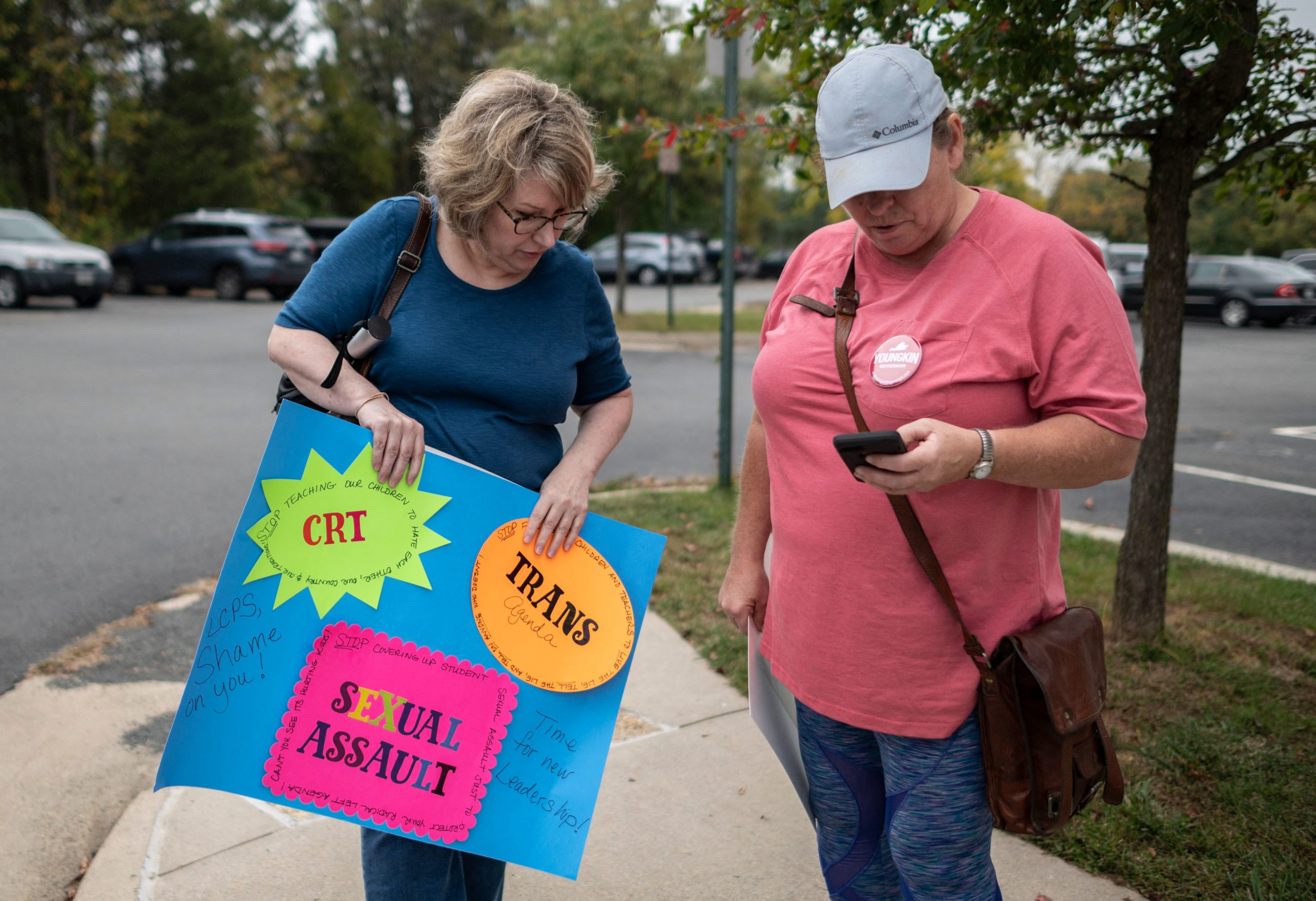 Protesters and activists stand outside a Loudoun County Public Schools (LCPS) board meeting in Ashburn, Virginia on October 12, 2021. (Photo by ANDREW CABALLERO-REYNOLDS/AFP via Getty Images)