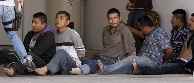 A drop house was raided by the Arizona Department of Public Safety along with other law enforcement jurisdictions including U.S. Immigration and Customs Enforcement, yielding nine suspected illegal immigrants, shown here, and three suspected human smugglers Thursday, April 29, 2010, in Phoenix. (AP Photo/Ross D. Franklin)