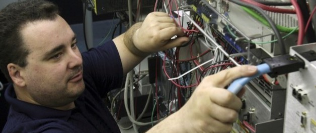 Network engineer Will Duquette adjusts power wires in a fuse panel at Great Works Internet in April in Biddeford, Maine. ( AP Photo/Pat Wellenbach)