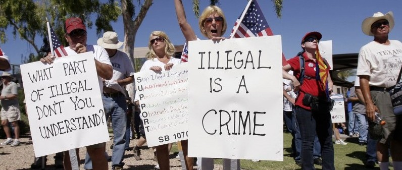 Judy Schulz, front, cheers as her husband Richard Schulz, left, both of Glendale, Ariz., as they joined hundreds supporting Arizona's new law on illegal immigration as they listen to speakers near the capitol Saturday, June 5, 2010, in Phoenix. (AP Photo/Ross D. Franklin)